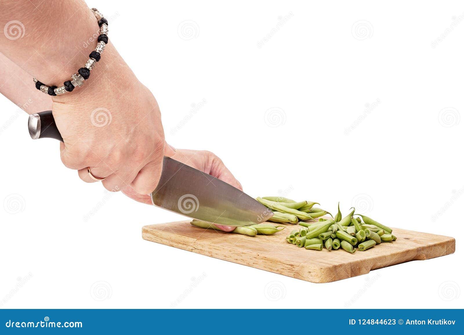 Pokrajać świeże fasolki szparagowe na tnącej desce na stole, biel ja