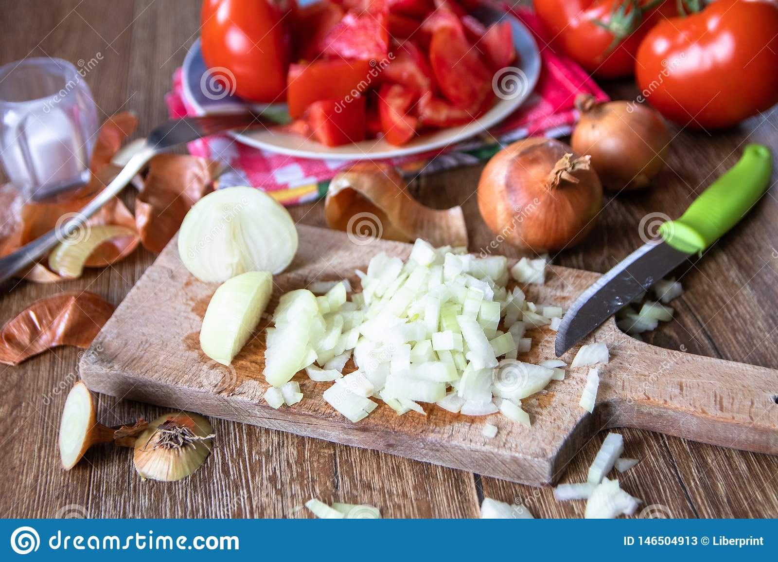 Pokrojona cebula na kuchni desce, ca?a cebula i pomidory w tle,