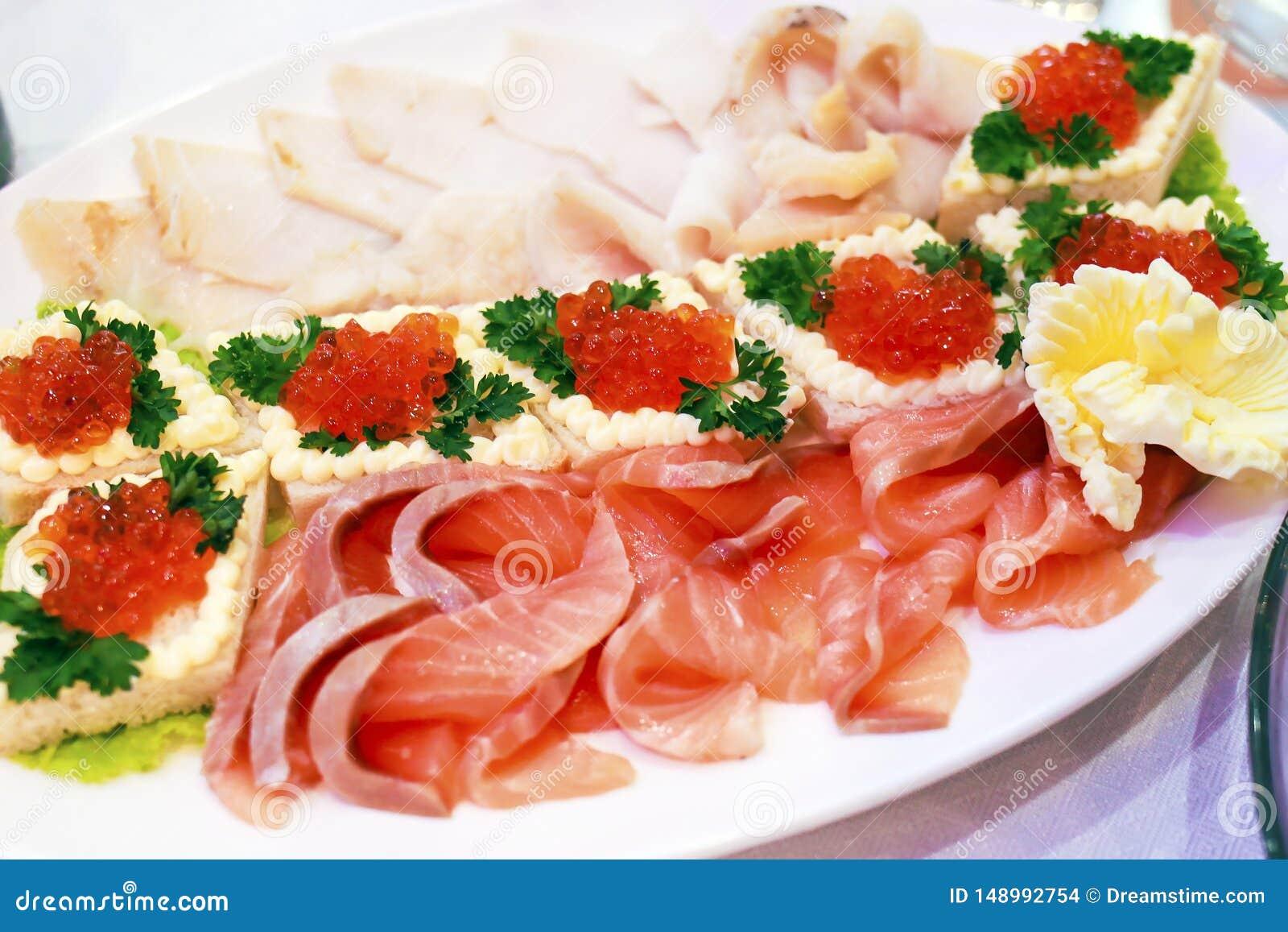Pokrojona ryba i piec kosz z czerwonym kawiorem na talerzu w restauracji
