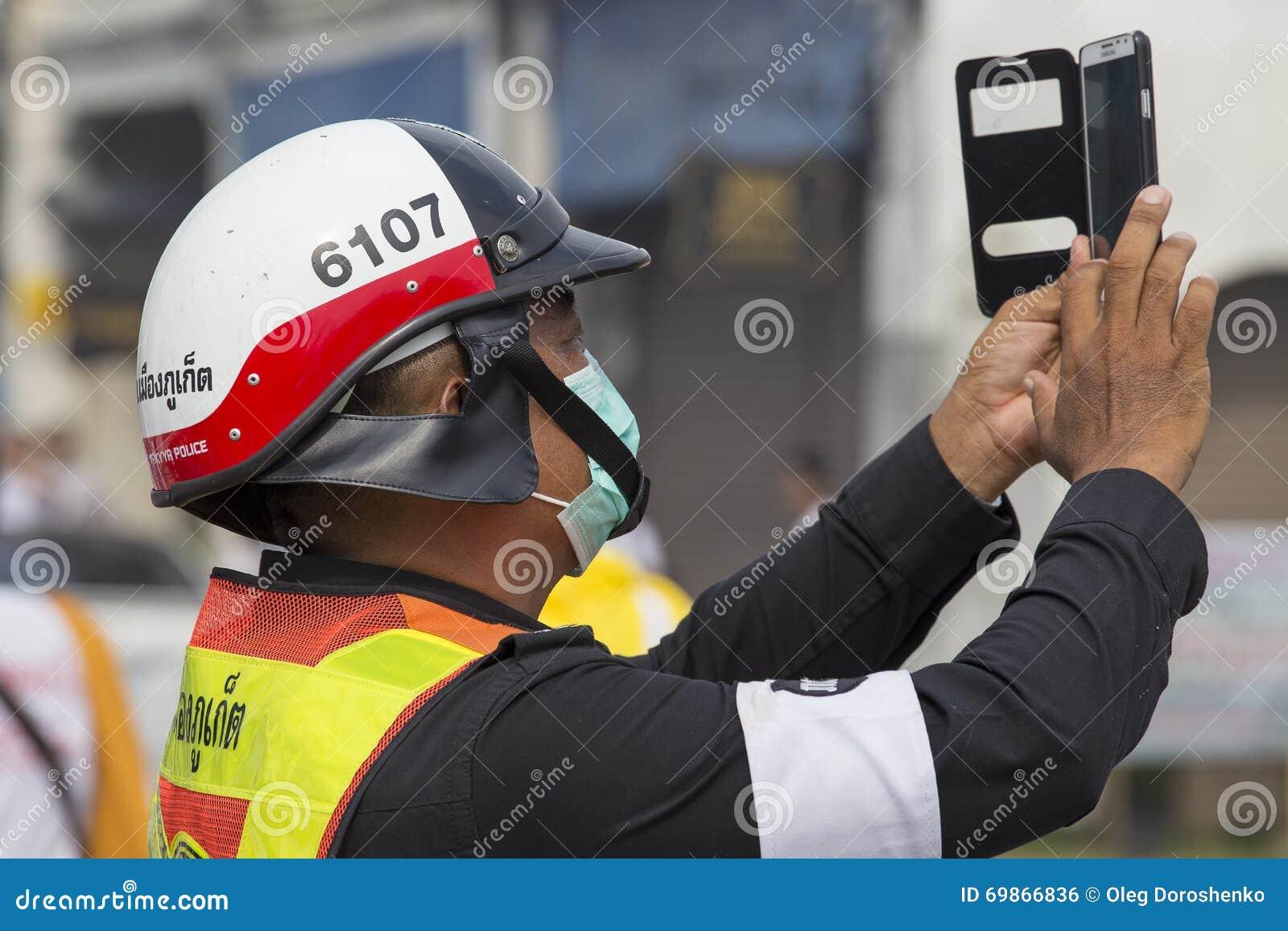 A polícia tailandesa fotografa na procissão do smartphone durante o festival do vegetariano na cidade de Phuket tailândia