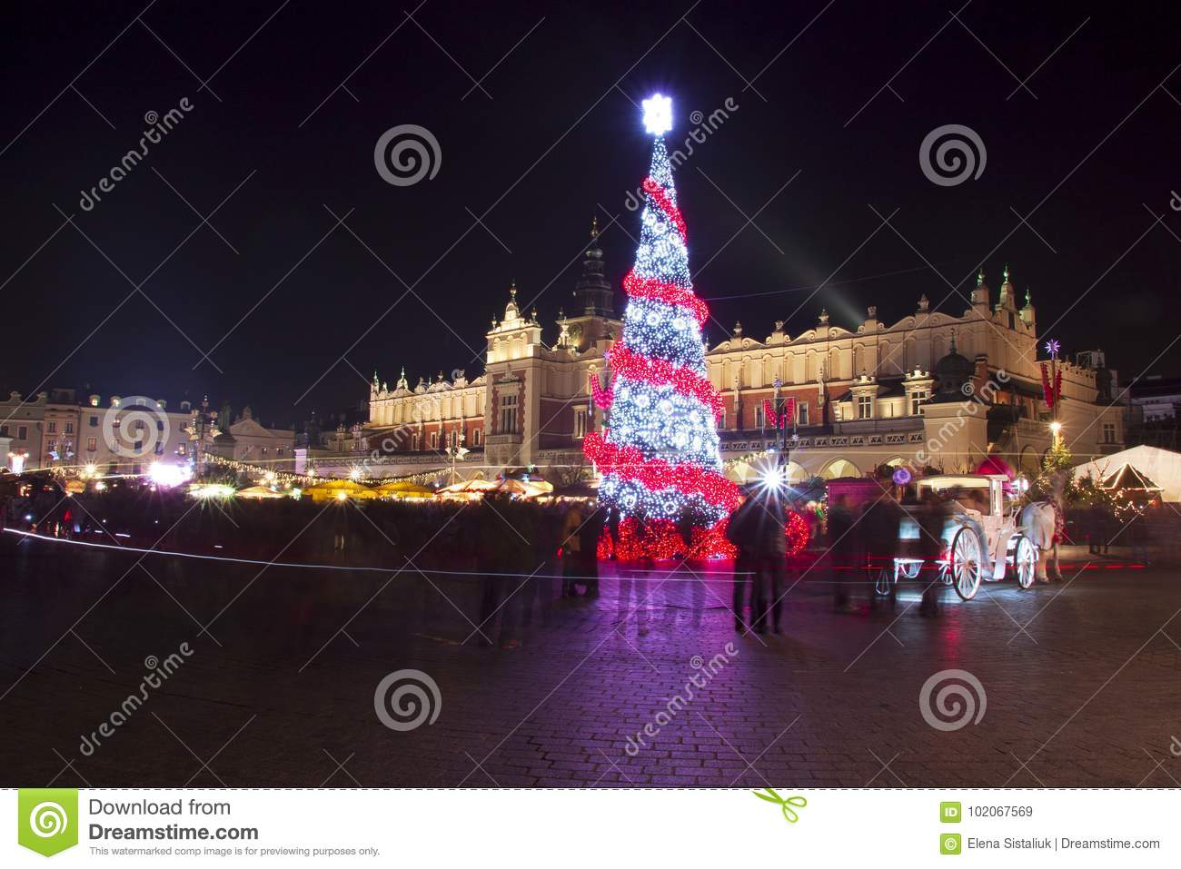 Poland, Krakow, Main Market square and Cloth Hall in winter, during Christmas fairs decorated with Christmas tree.