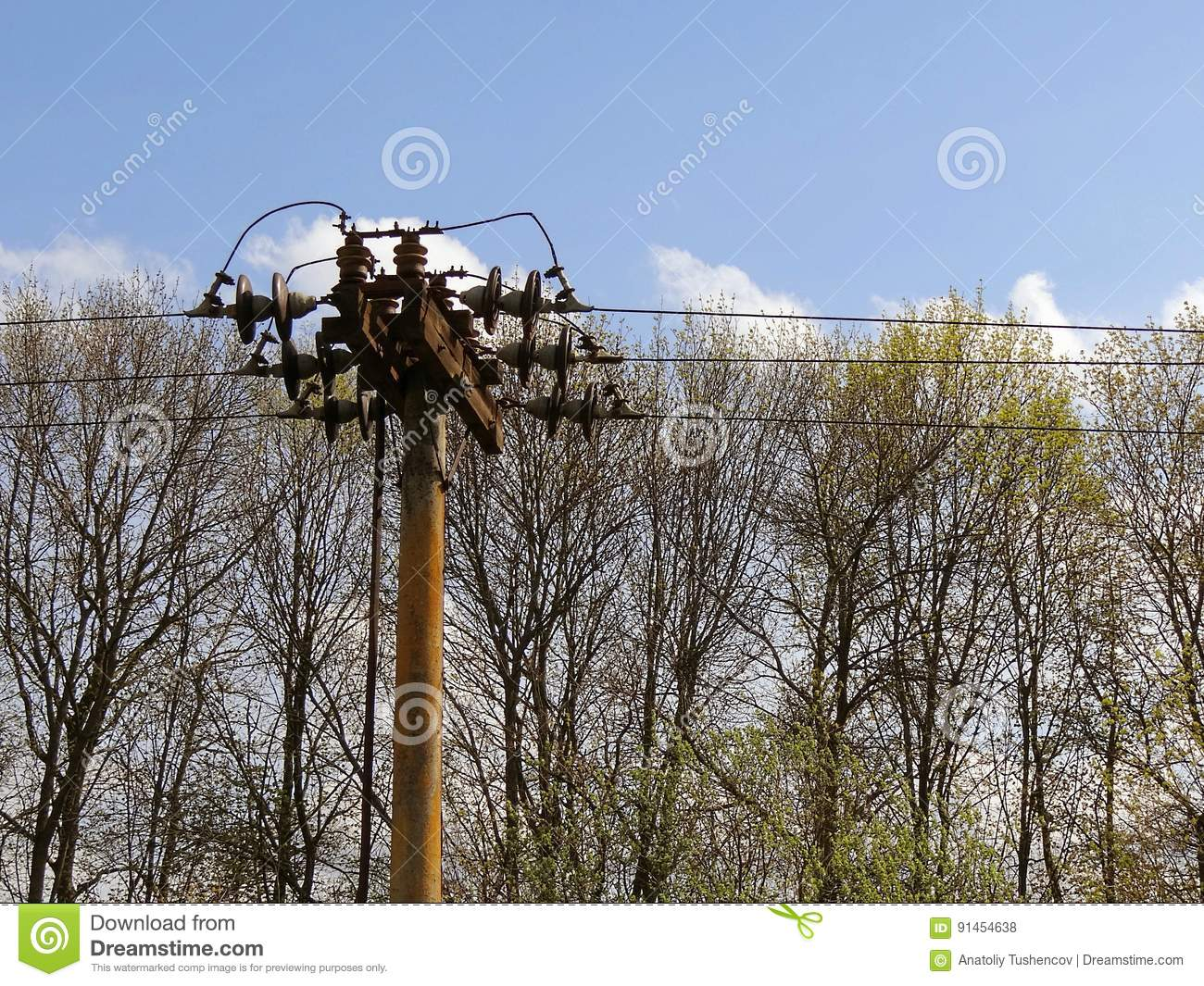 Man On High Voltage Wire : The pole with high voltage wires against sky and trees