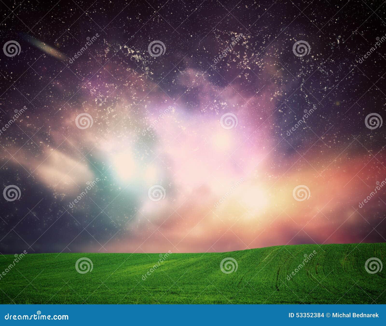 Pole trawa pod wymarzonym galaxy niebem, przestrzeń, jarzy się gra główna rolę
