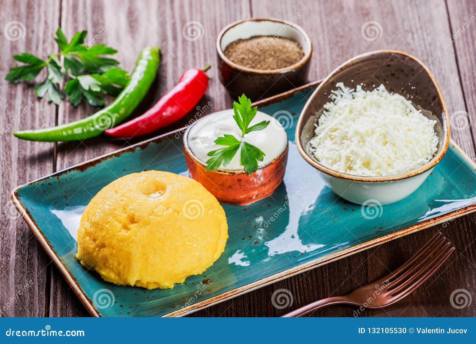 Polenta delicioso - sémola de maíz de las gachas de avena del maíz con queso, mantequilla y crema agria de cabra en fondo de made