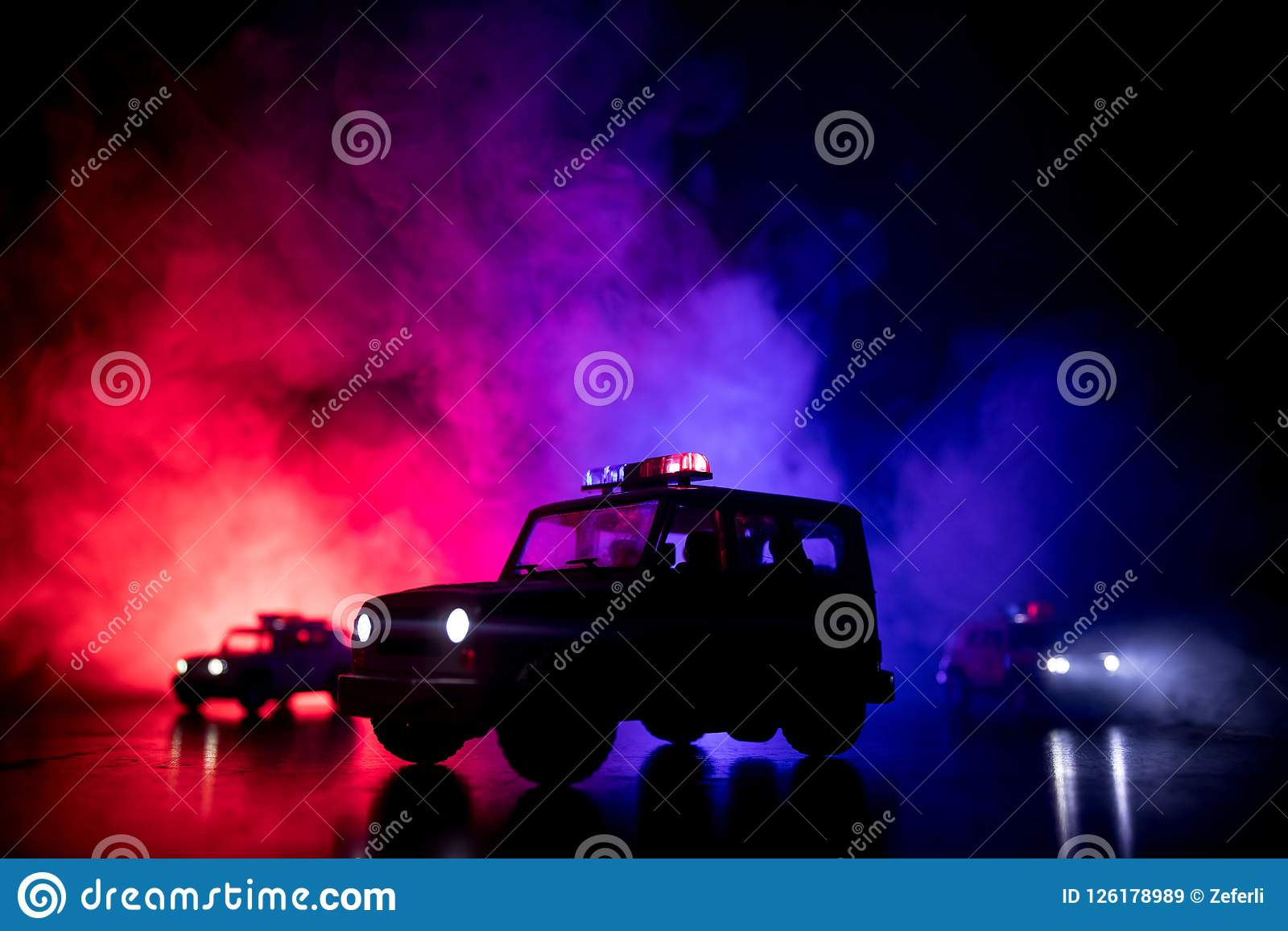Police car chasing a car at night with fog background. 911 Emergency response police car speeding to scene of crime. Selective foc