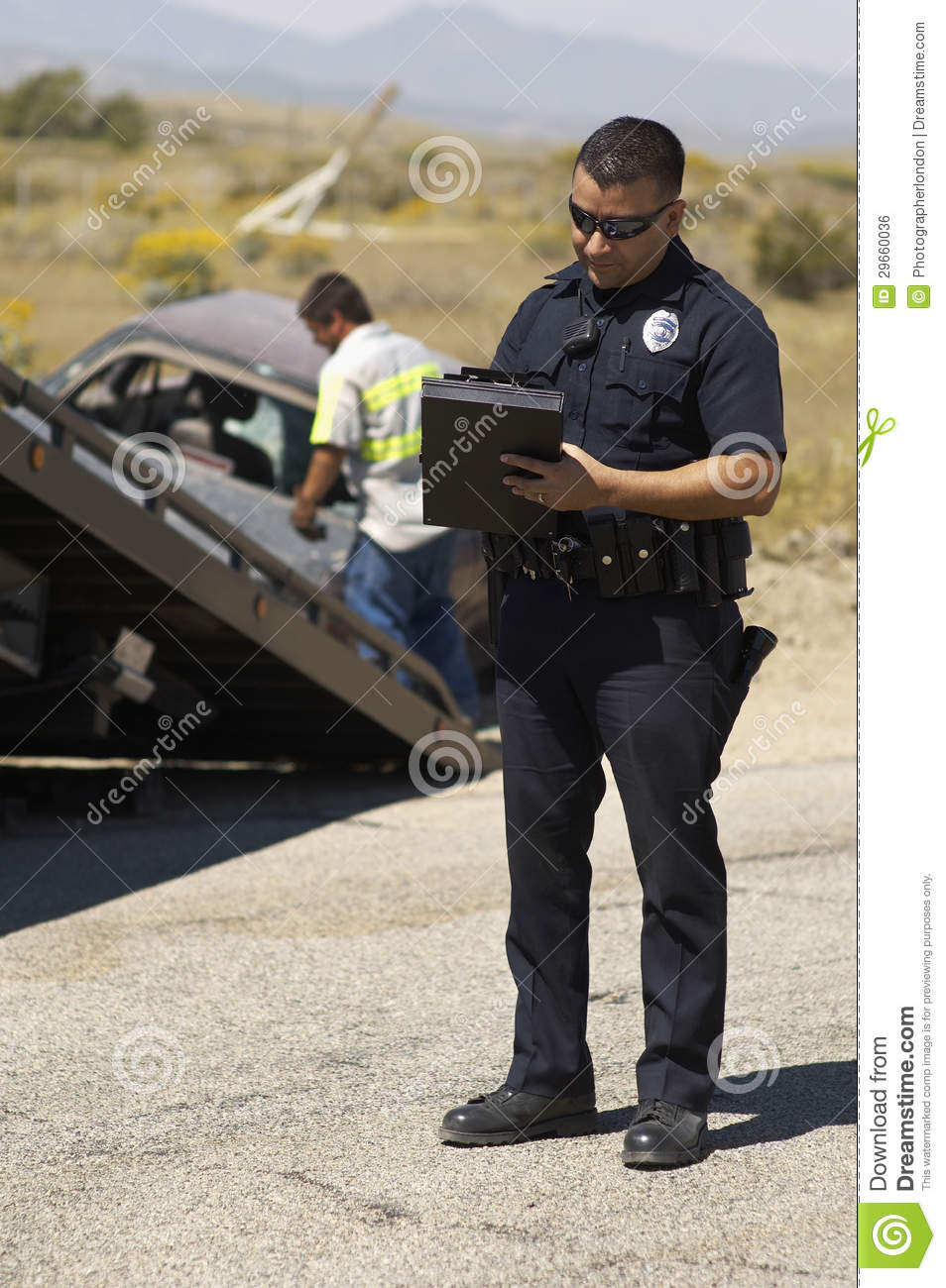 police officer writing notes at car crash scene royalty