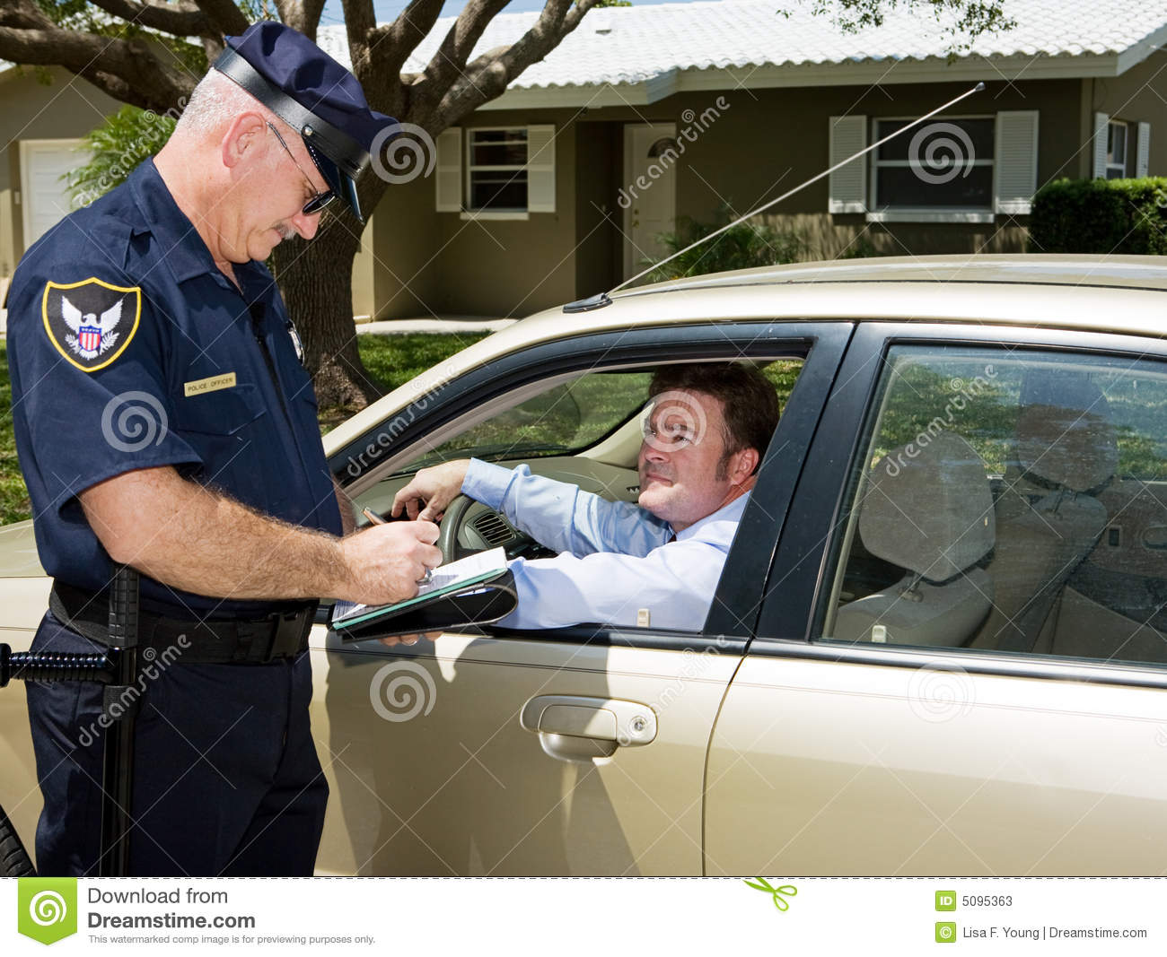 Police officer writing a traffic citation while an unfortunate driver ...