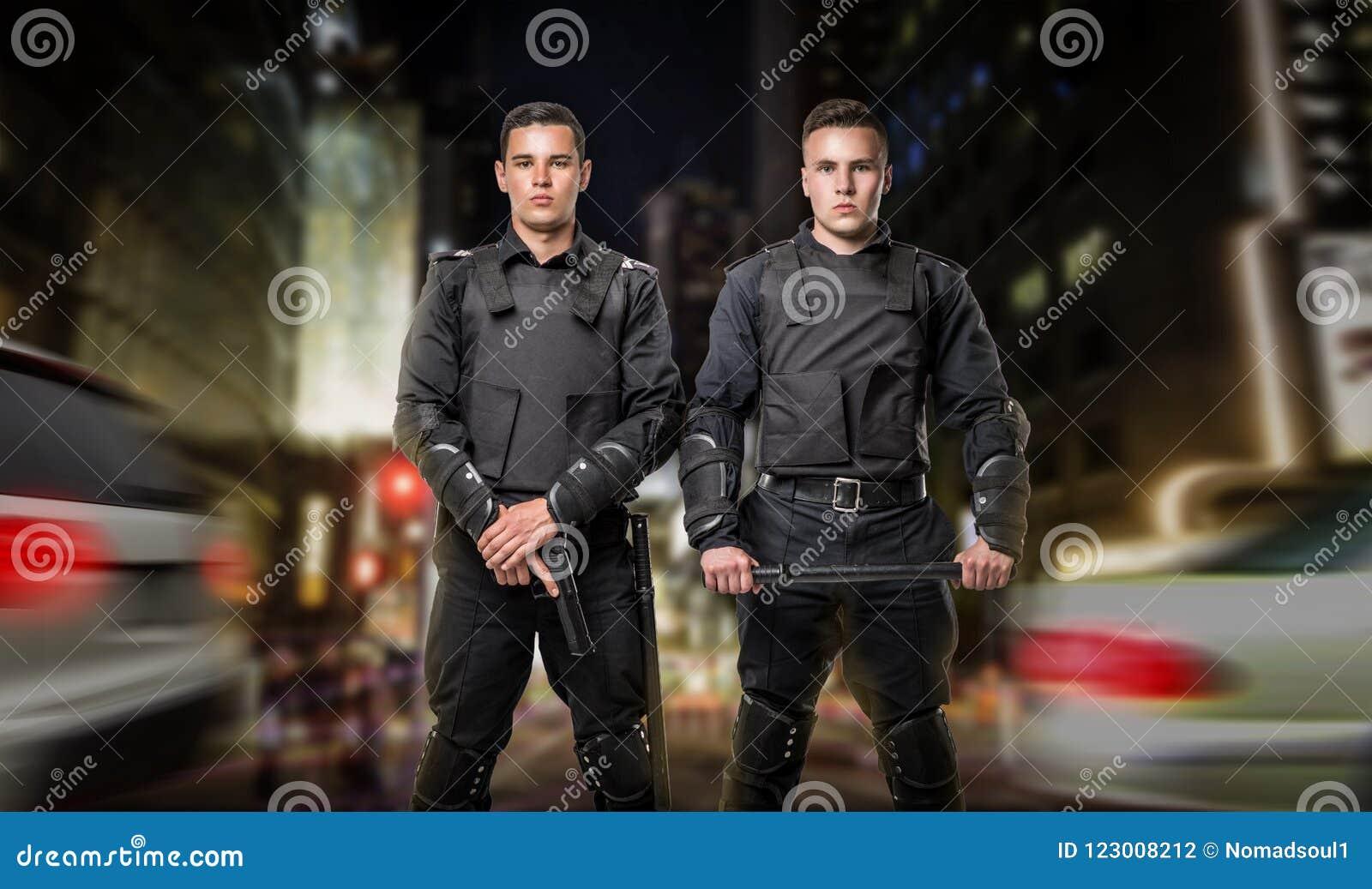Polis con el arma y un bastón en el guardia de la ley