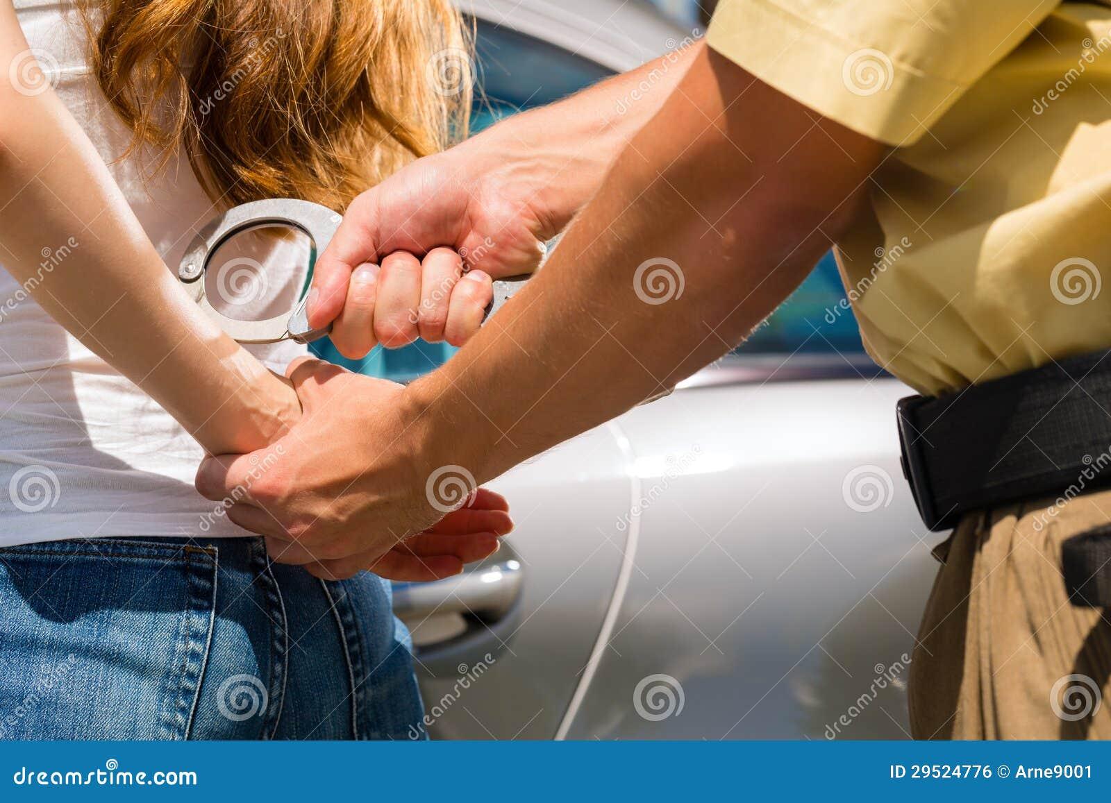 Polis som arresterar en kvinna med handbojor