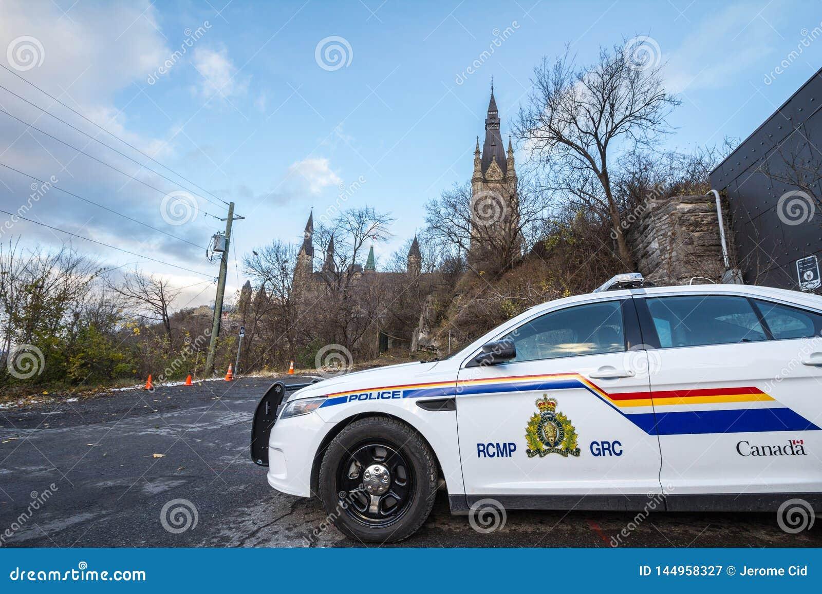 Polisbil för RCMP som GRC framme står av den kanadensiska parlamentbyggnaden