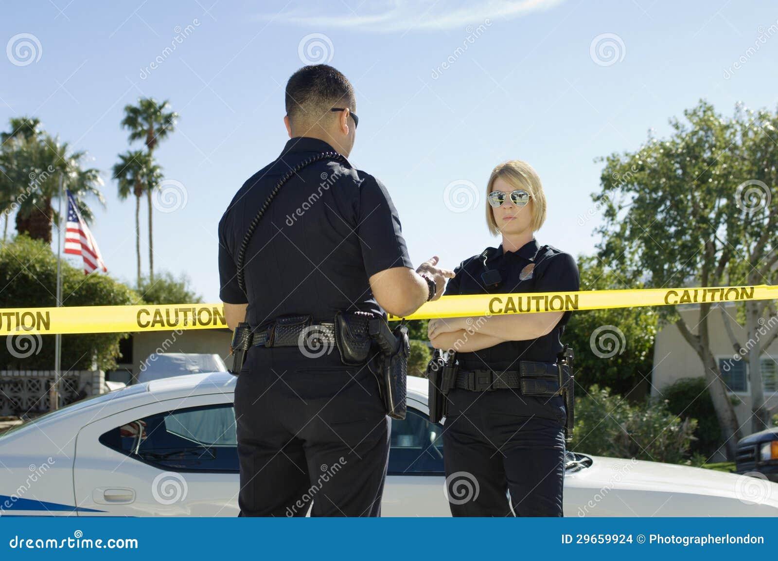 Poliser som avskiljs av varningsbandet