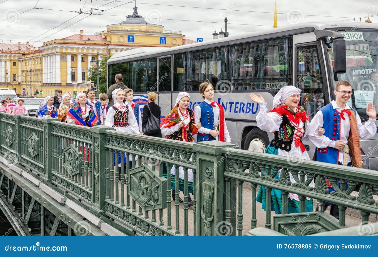 Polish folk dance ensemble GAIK are passing to the point of the performance over the Dvortsoviy bridge.