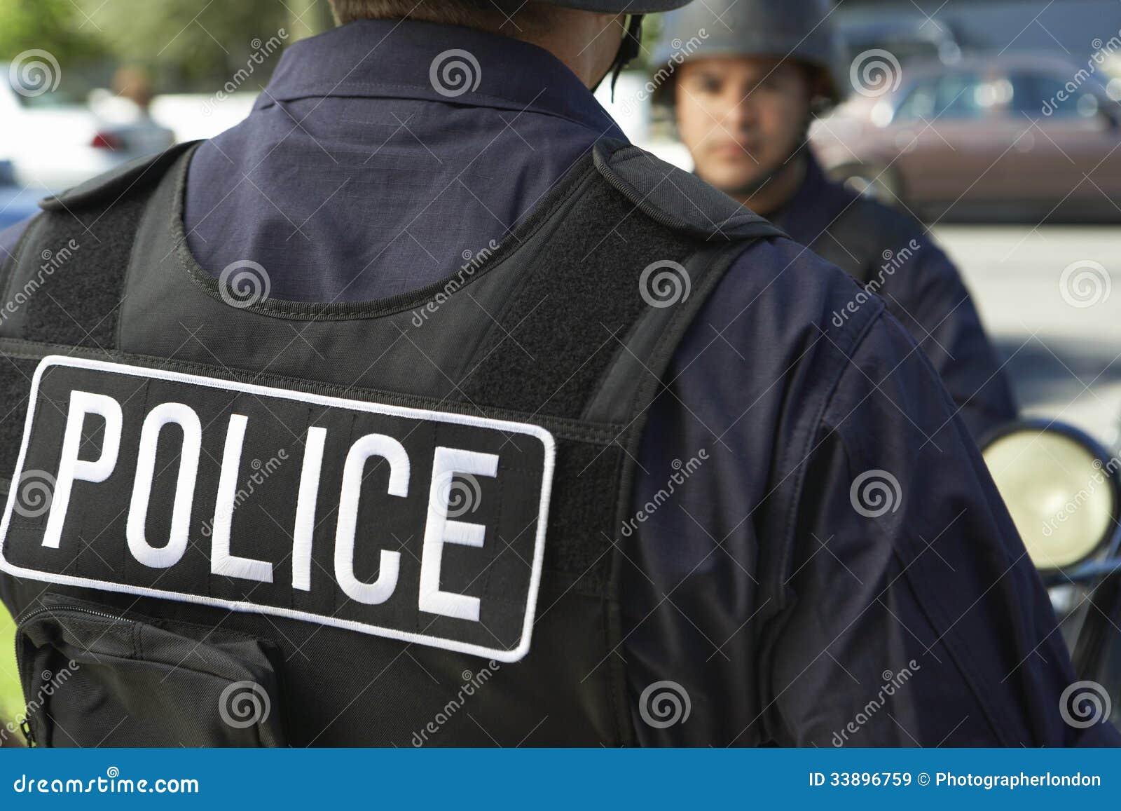 Politieagent die Beschermend Vest in openlucht dragen