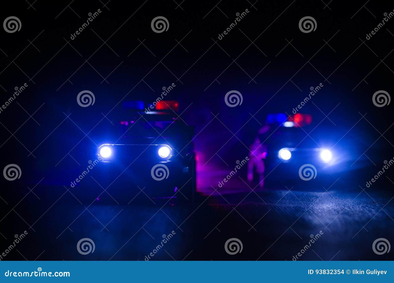 Politiewagen die een auto achtervolgen bij nacht met mistachtergrond 911 de politiewagen van de noodsituatiereactie het verzenden