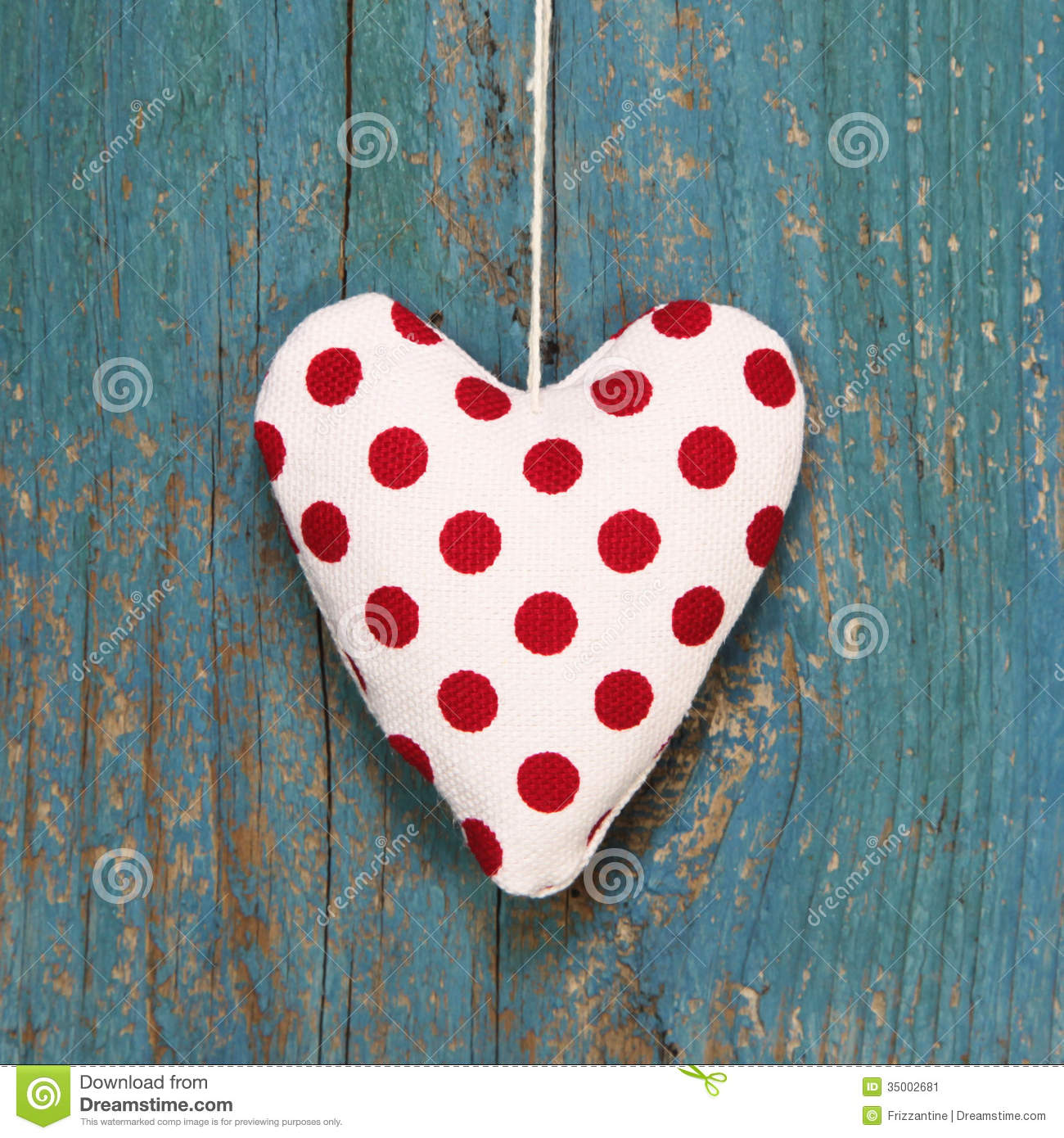Polka dotted heart on turquoise wooden surface in country style.