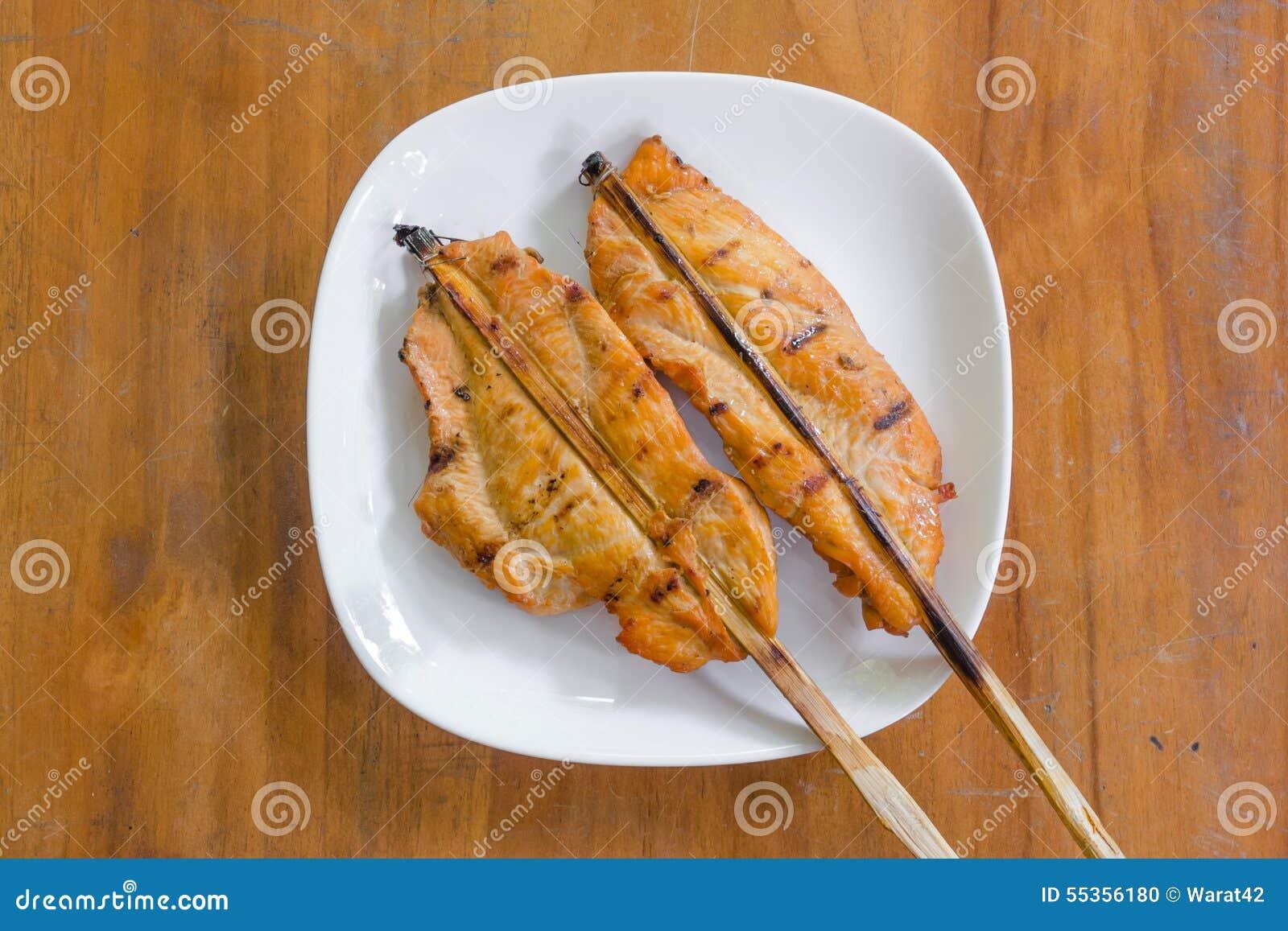 Pollo arrostito sul piatto bianco, fondo di legno
