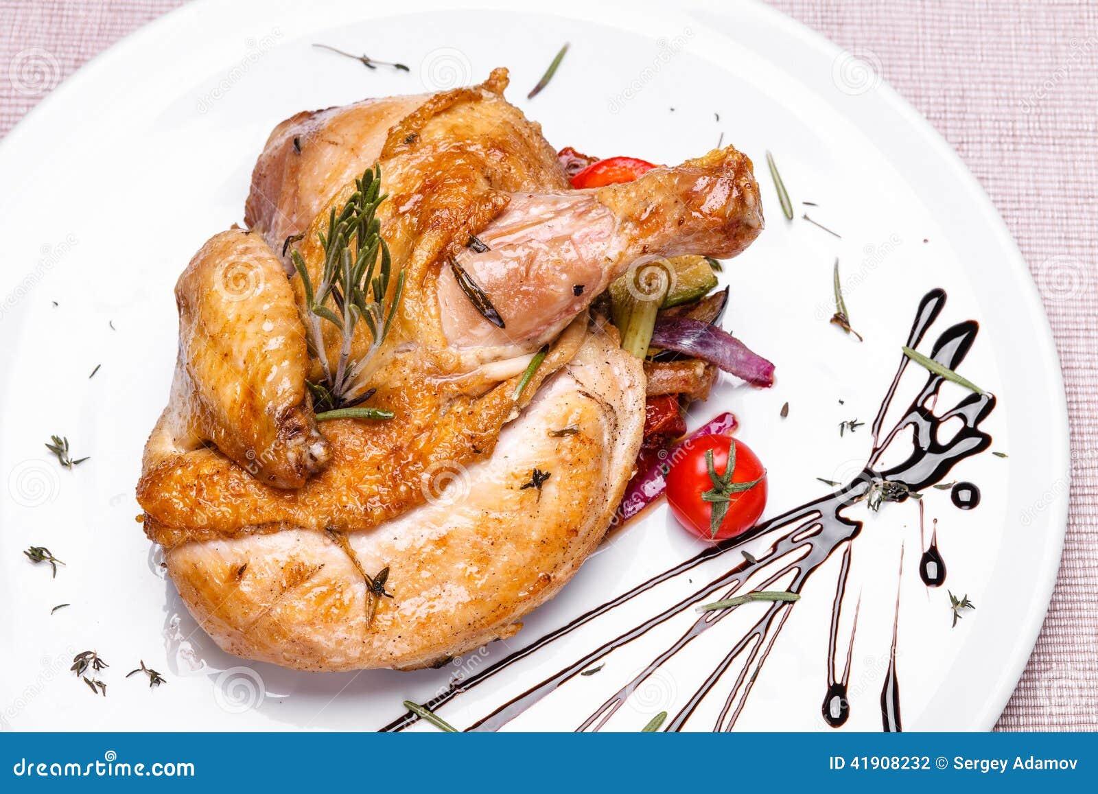 Pollo asado con romero en una placa blanca