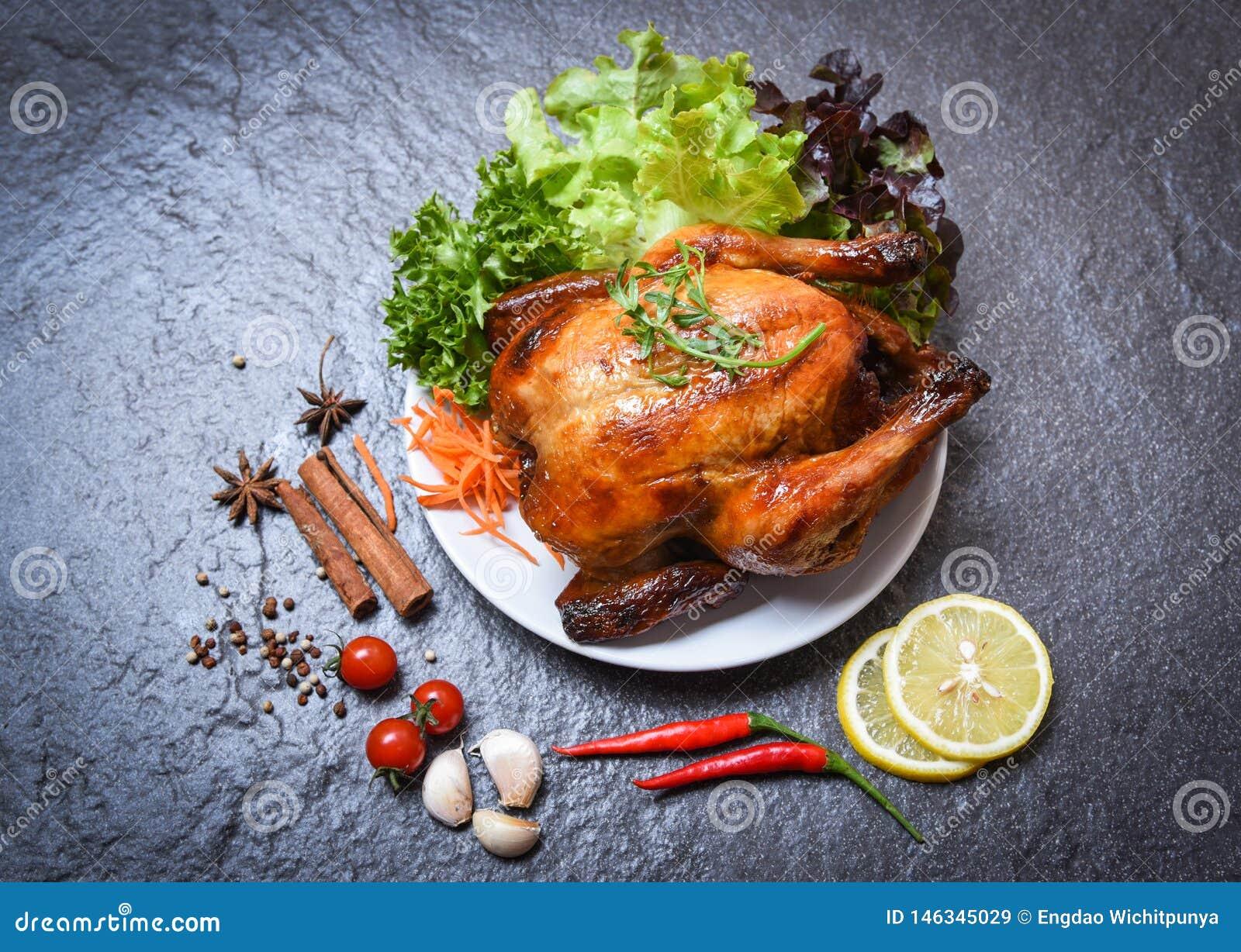 Pollo asado/pollo entero cocido asado a la parrilla en la placa con las hierbas y especias y fondo oscuro