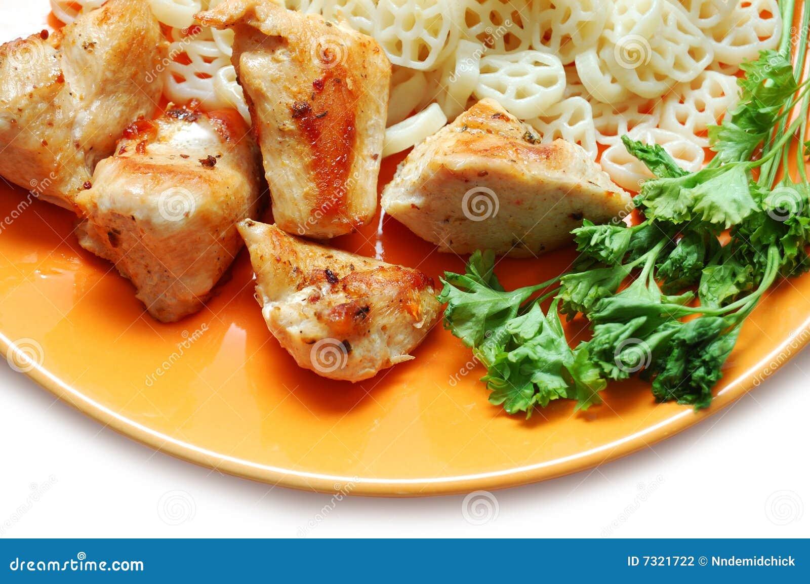 Pollo fritto, pasta e prezzemolo sulla zolla arancione