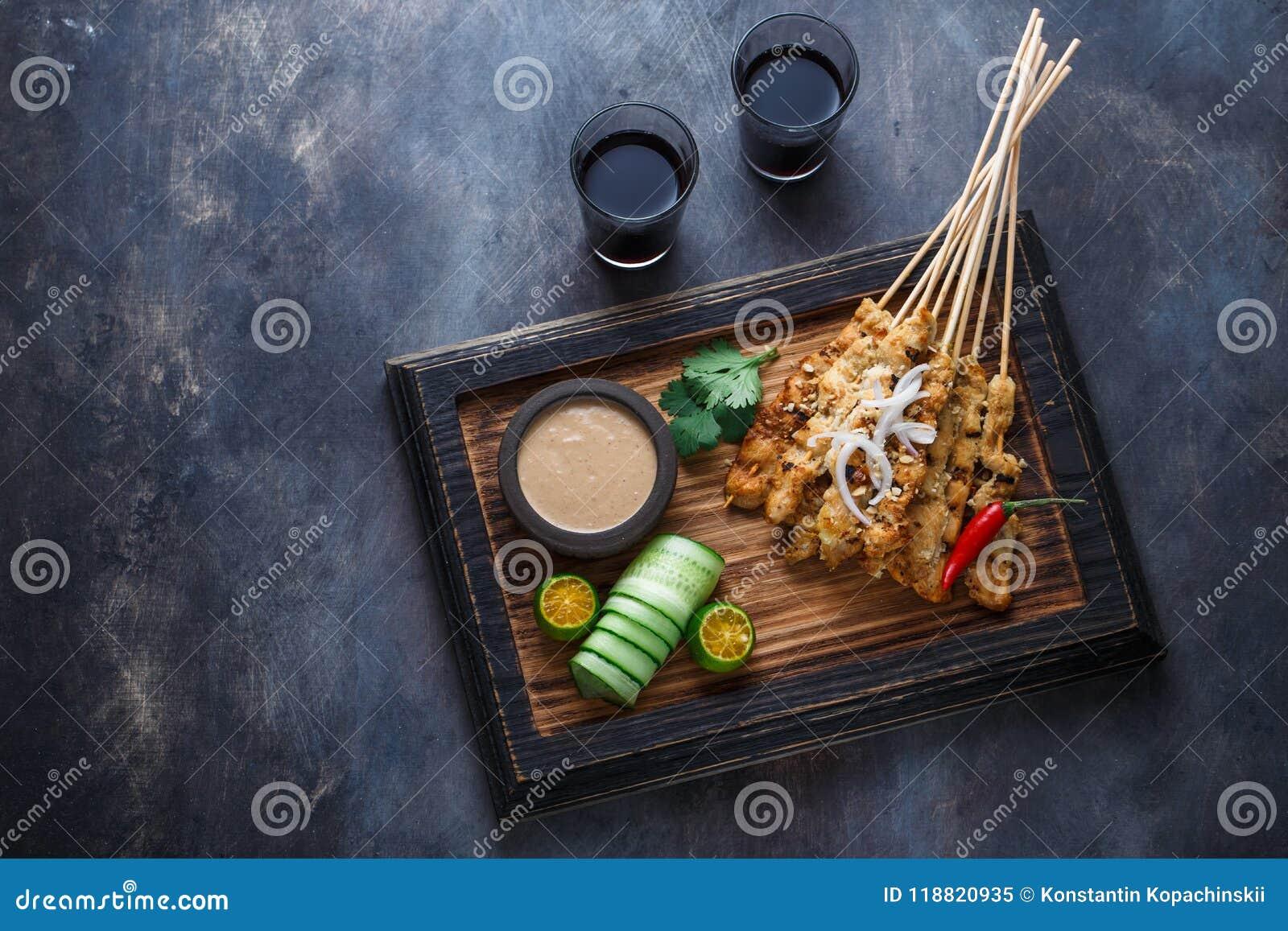 Pollo Satay o Sate Ayam - comida famosa del malasio Es un plato de la carne sazonada, ensartada y asada a la parrilla, servida co