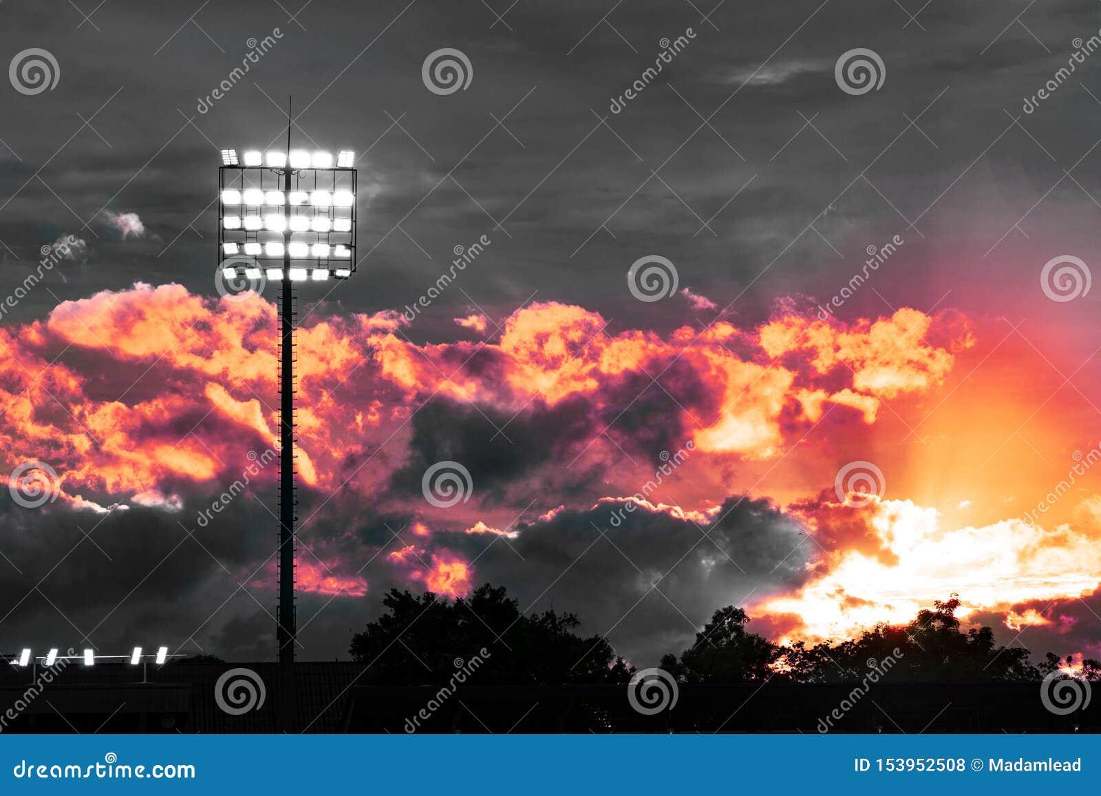 Polo eléctrico ligero blanco en el estadio del deporte con dramáticamente el cielo y el cielo rojo de la tarde de la luz anaranja