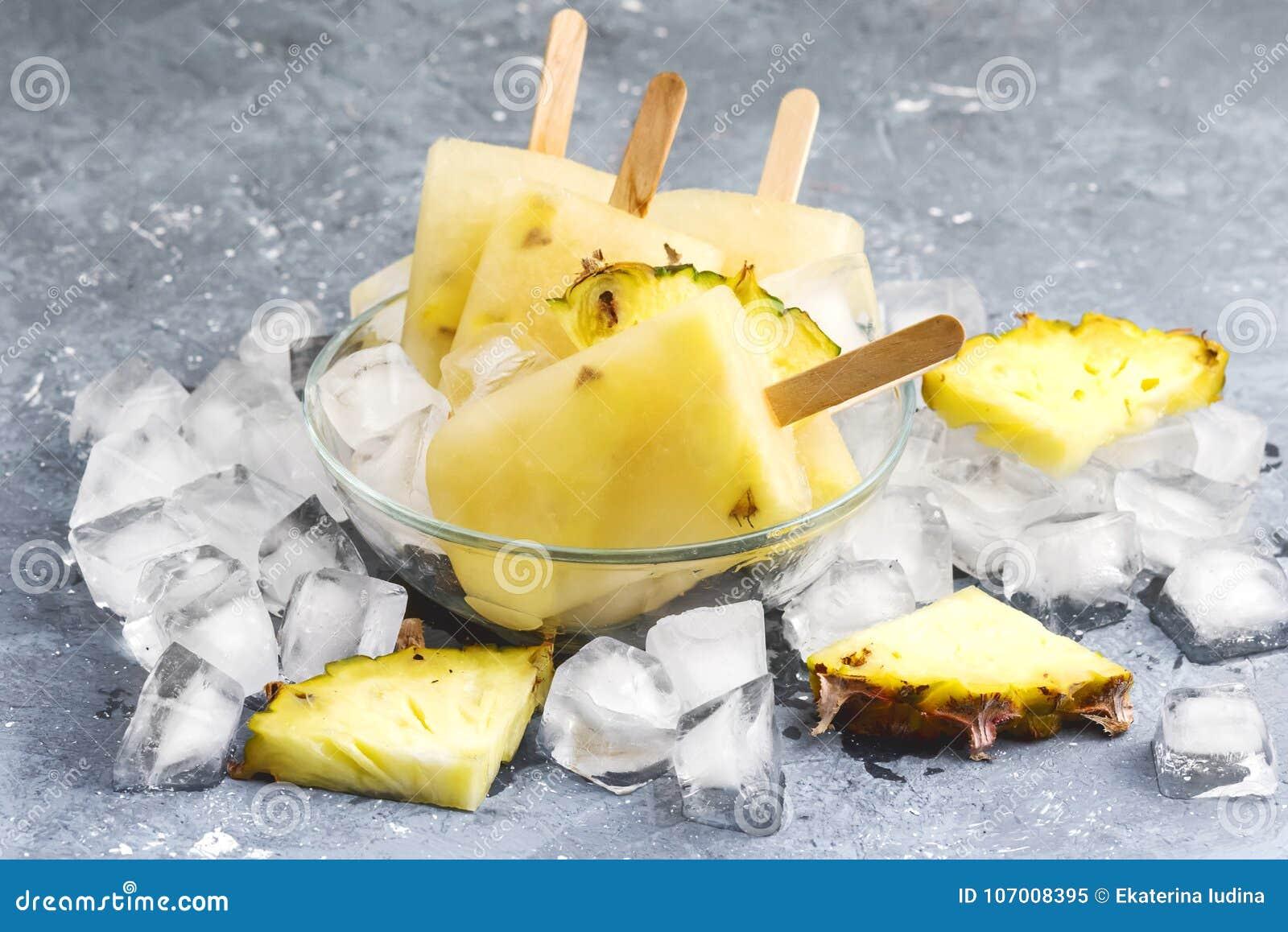 Polos hechos en casa deliciosos de la piña en los cubos de hielo Gray Background Summer Food Concept sobre horizontal