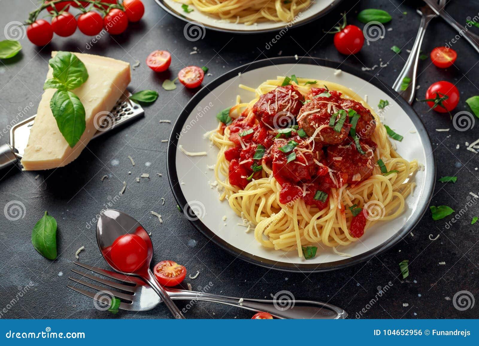 Polpette della pasta degli spaghetti con salsa al pomodoro, basilico, parmigiano delle erbe su fondo scuro