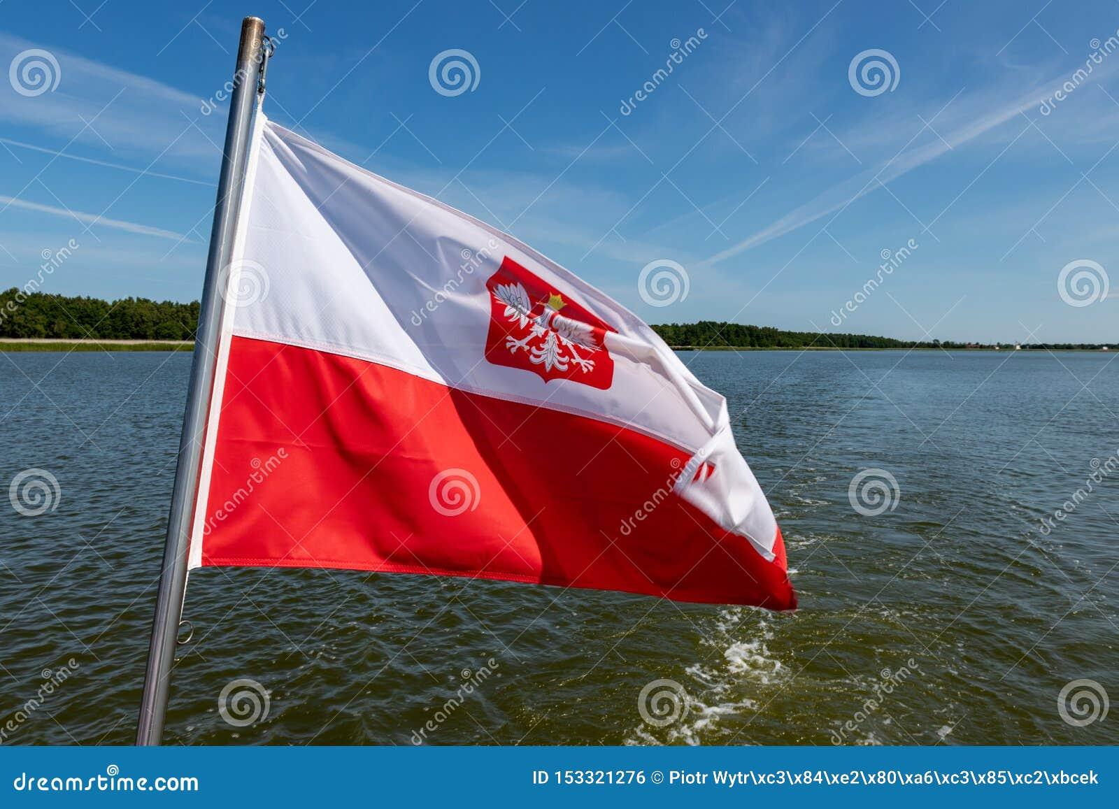 Polska flaga zawieszająca na srogo mały śródlądowy statek Naczynie unosi się na wielkim jeziorze w środkowym Europa