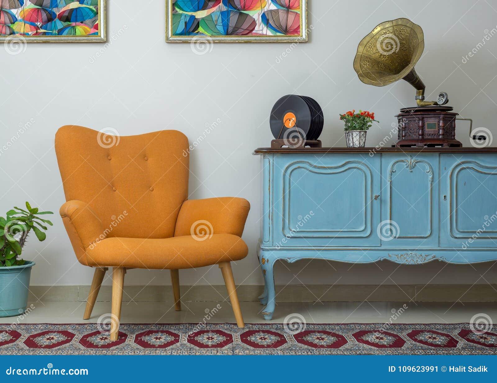 Poltrona alaranjada retro, luz de madeira do vintage - aparador azul, gramofone velho do fonógrafo, registros de vinil e candeeir