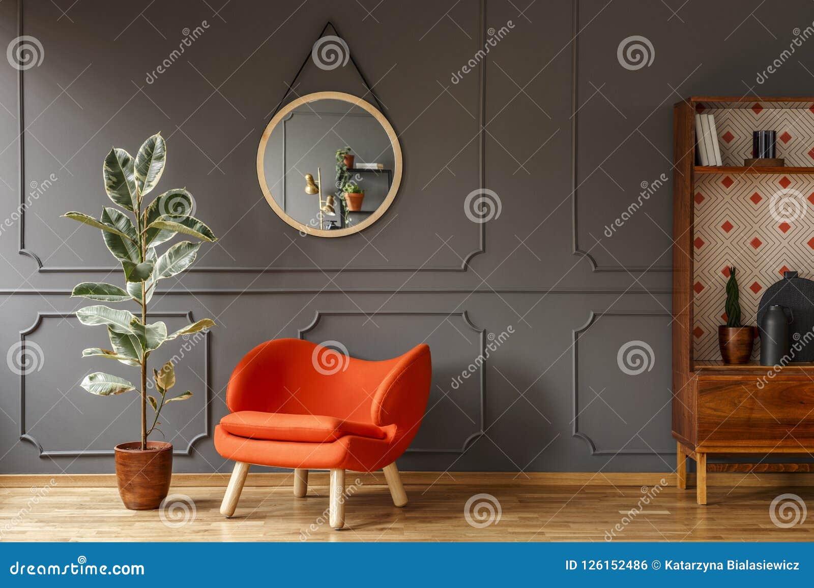 Poltrona arancio luminosa, un retro gabinetto di legno e uno specchio sulla a