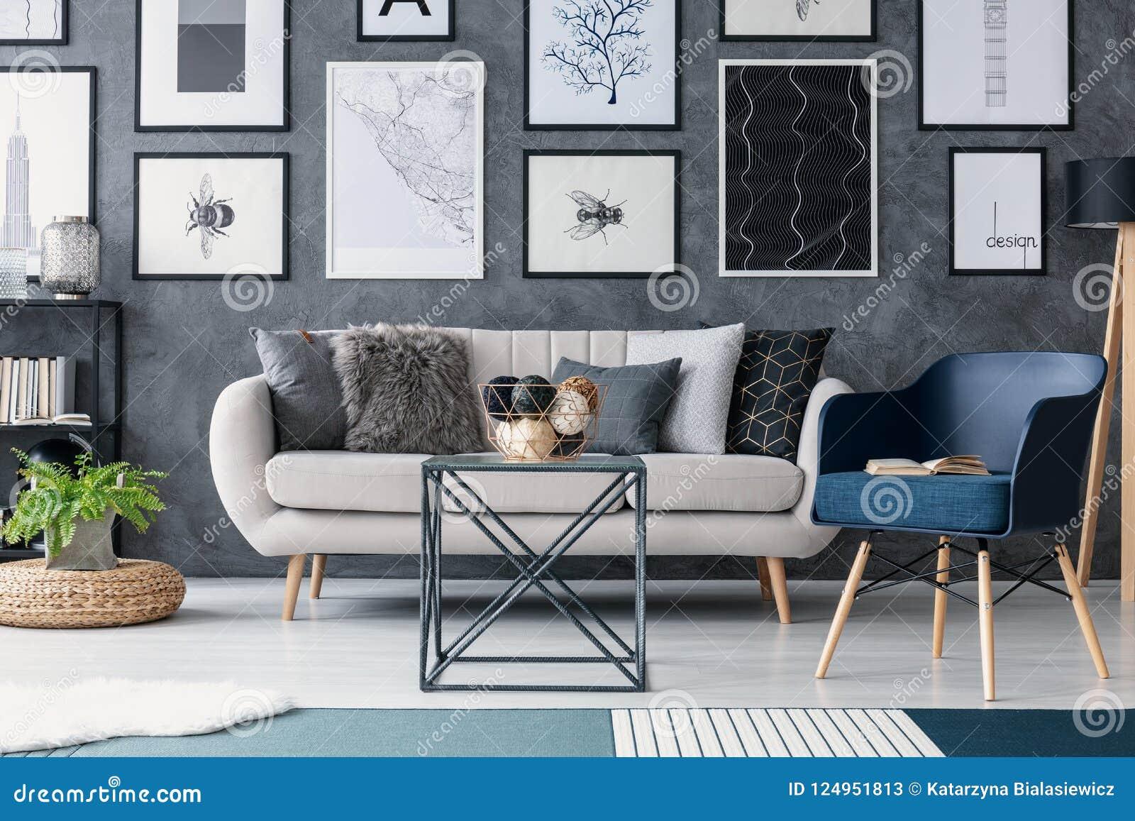 Poltrona azul ao lado do sofá e da tabela no interior da sala de visitas com cartazes e planta no pufe Foto real