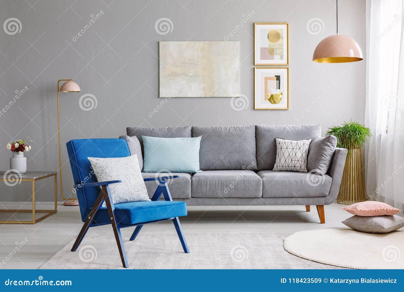 Poltrona azul perto do canapé cinzento em wi interiores da sala de visitas moderna