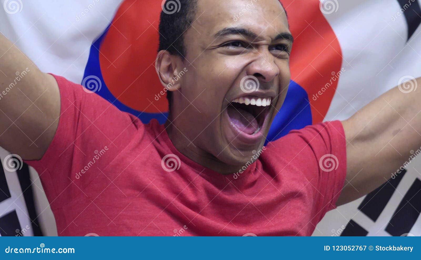 Poludniowo-koreański fan świętuje trzymający flaga Południowy Korea w zwolnionym tempie