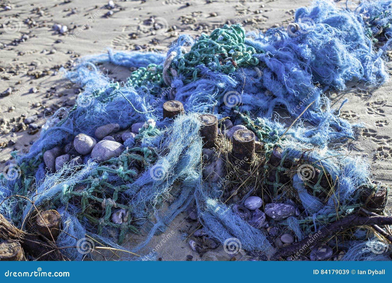 Poluição plástica - o azul tangled as redes de pesca lavadas acima no b