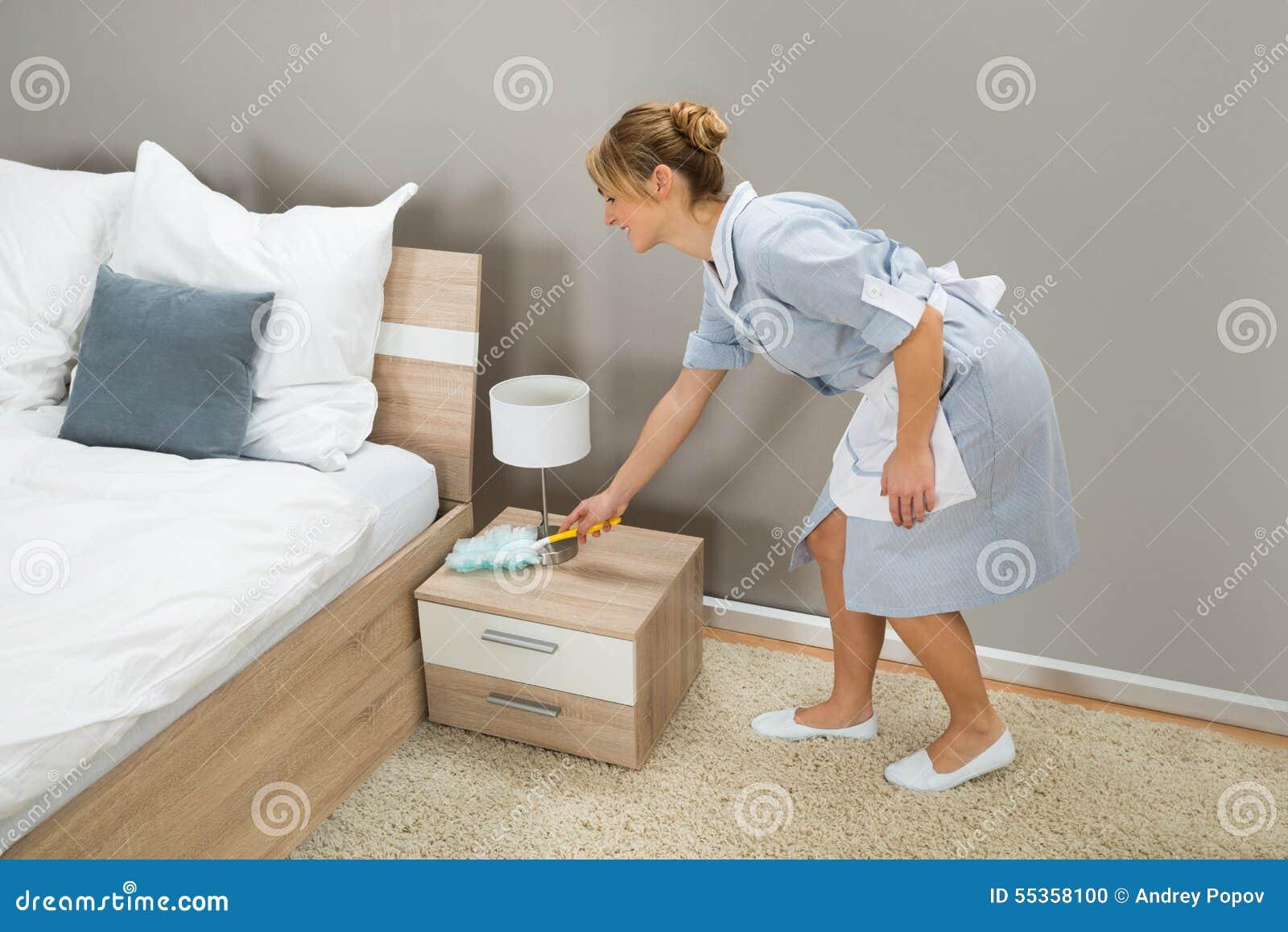 Polvere di pulizia della domestica con lo spolveratore della piuma