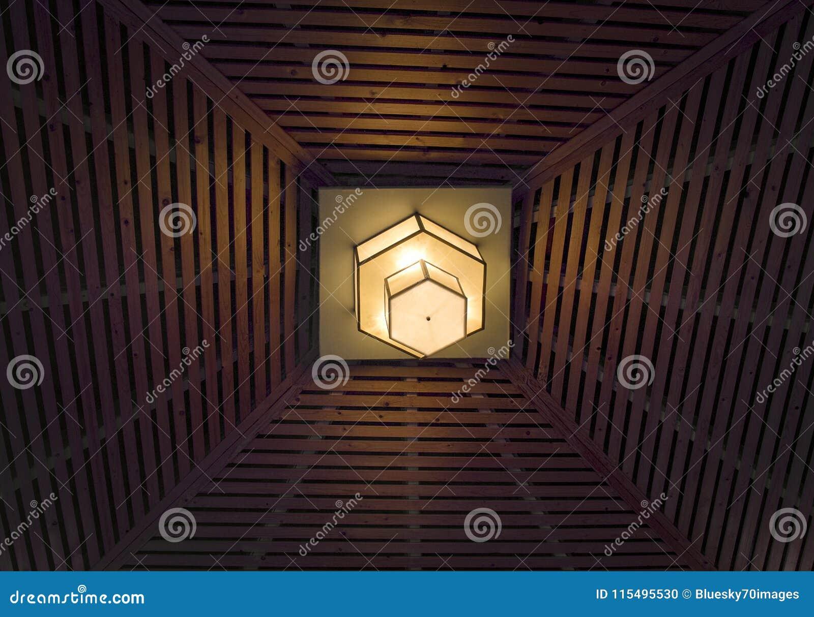 Polygonal Design Lamp Glowing On Kiosk Ceiling Stock Photo