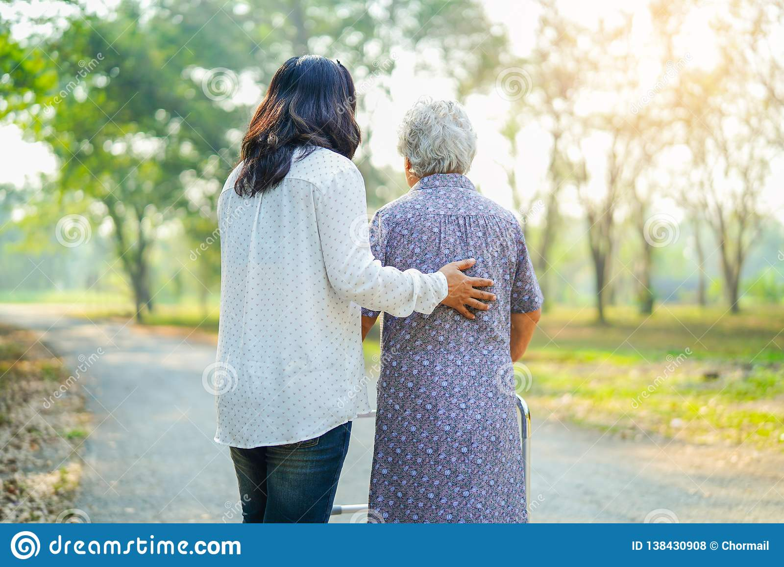 Pomaga Azjatyckiego seniora i dba lub starsza starej damy kobieta używa piechura z silnymi zdrowie przy parkiem w szczęśliwym wak