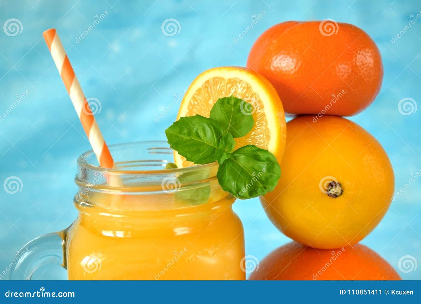 Pomarańcze, cytryna, mandarynka i koloru żółtego sok w szklanym słoju,