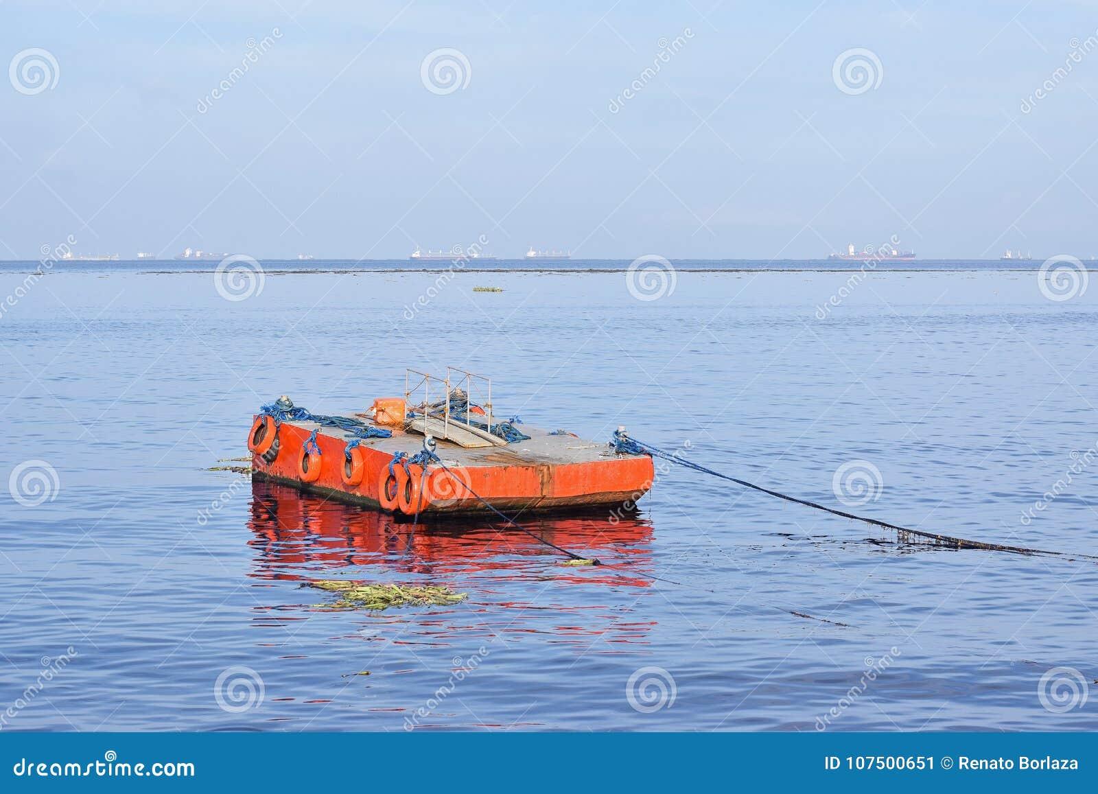Pomarańcze malująca metal barka zakotwiczał wzdłuż ocean zatoki