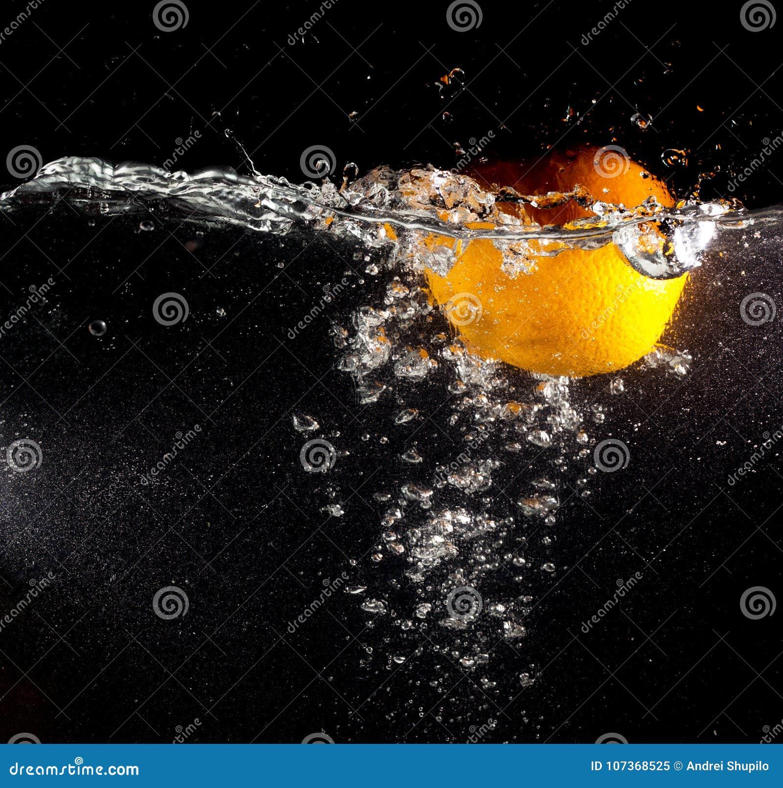 Pomarańcze pod wodą na czarnym tle