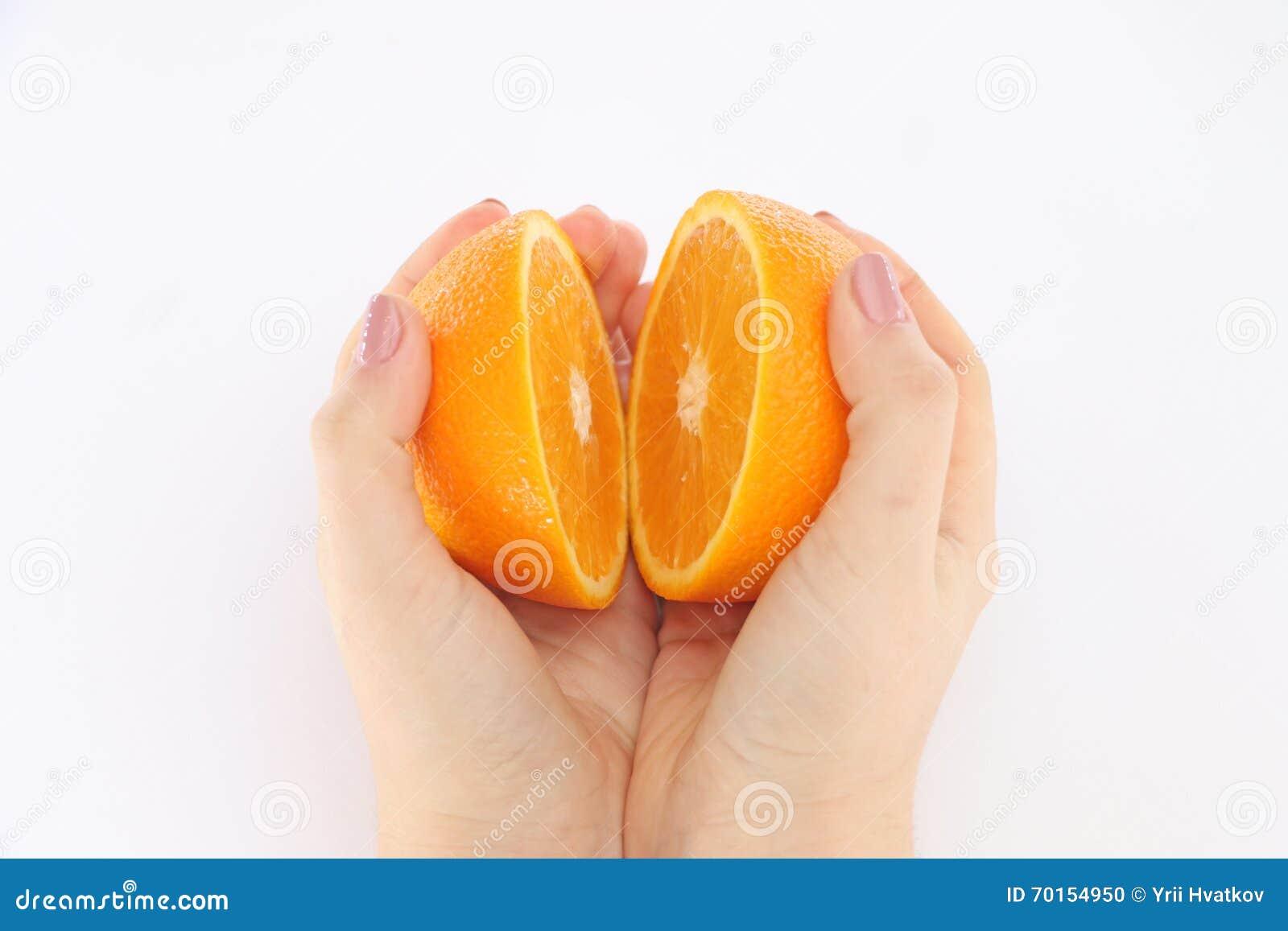 Pomarańcze w cięciu w jego ręki