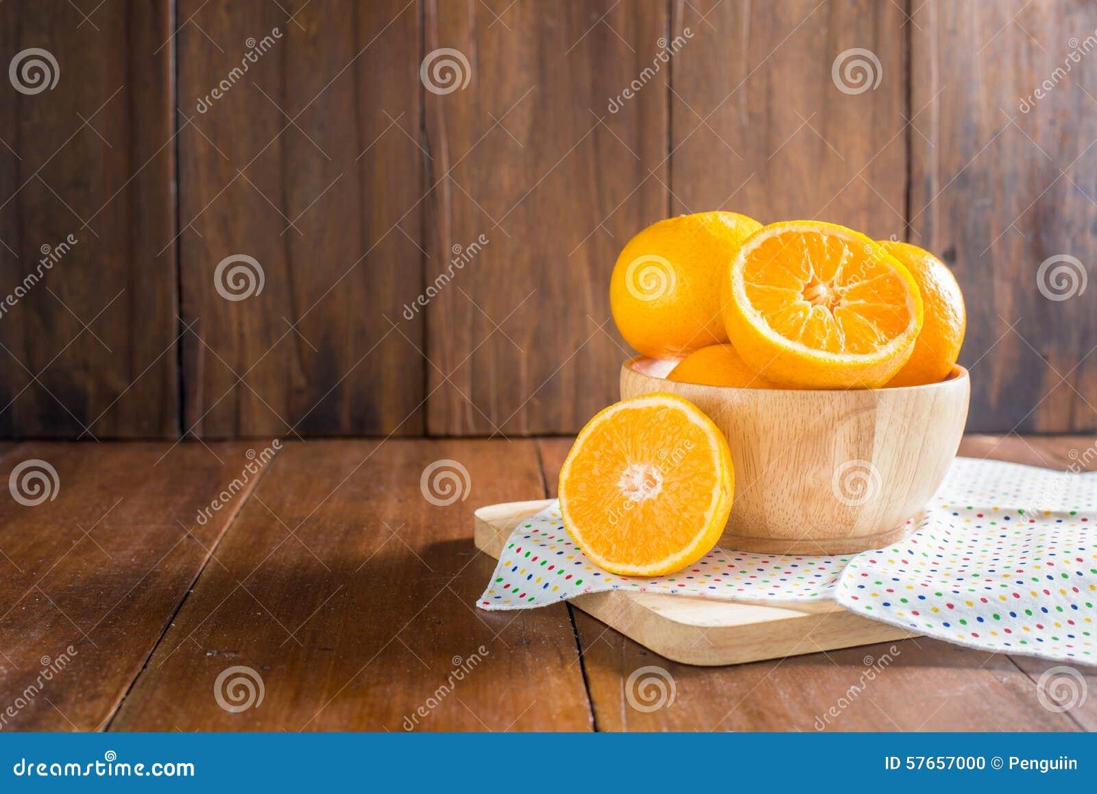 Pomarańcze w drewnianym pucharze na drewnianym tle