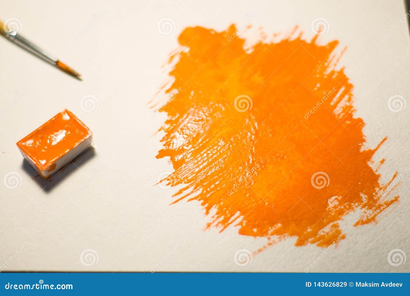 Pomarańczowa postać malująca z akwarelą
