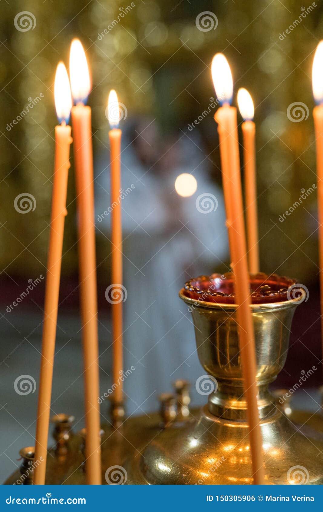 Pomarańczowe świeczki stojaka w żelaznym candlestick i ogieniu zaświecają