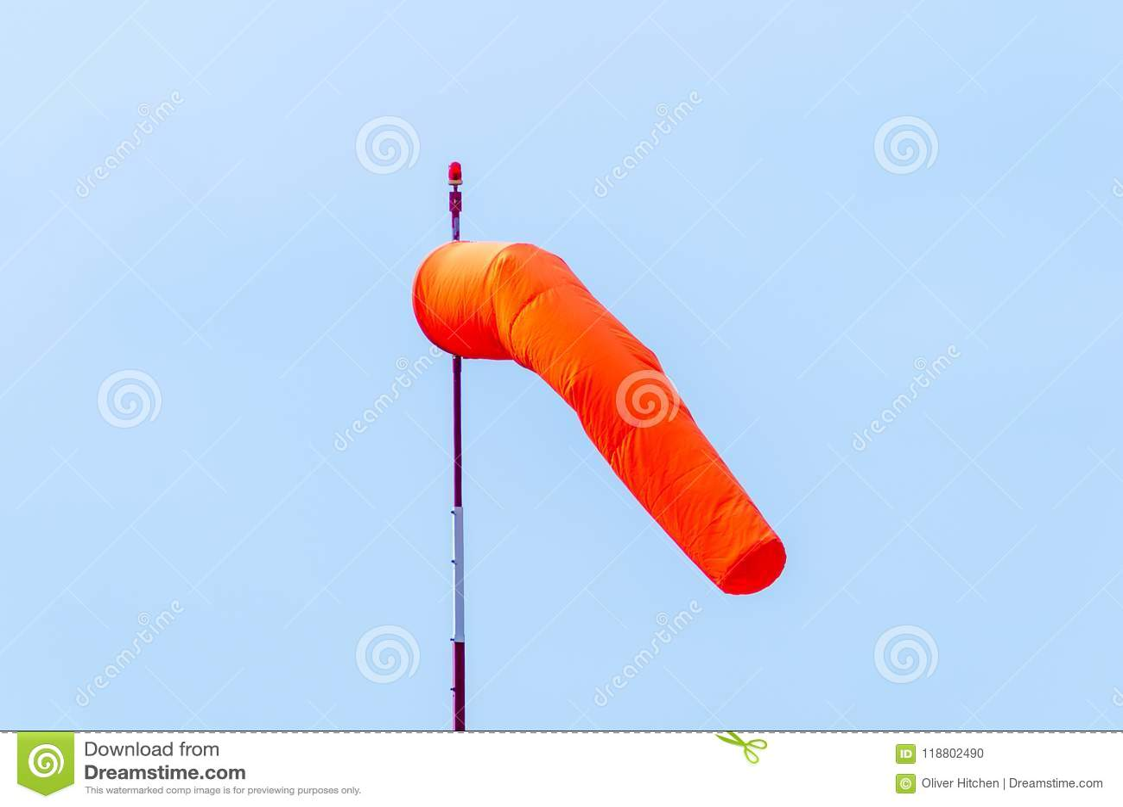 Pomarańczowego lotniska wiatrowa skarpeta na białym i czerwonym słupie z czerwienią