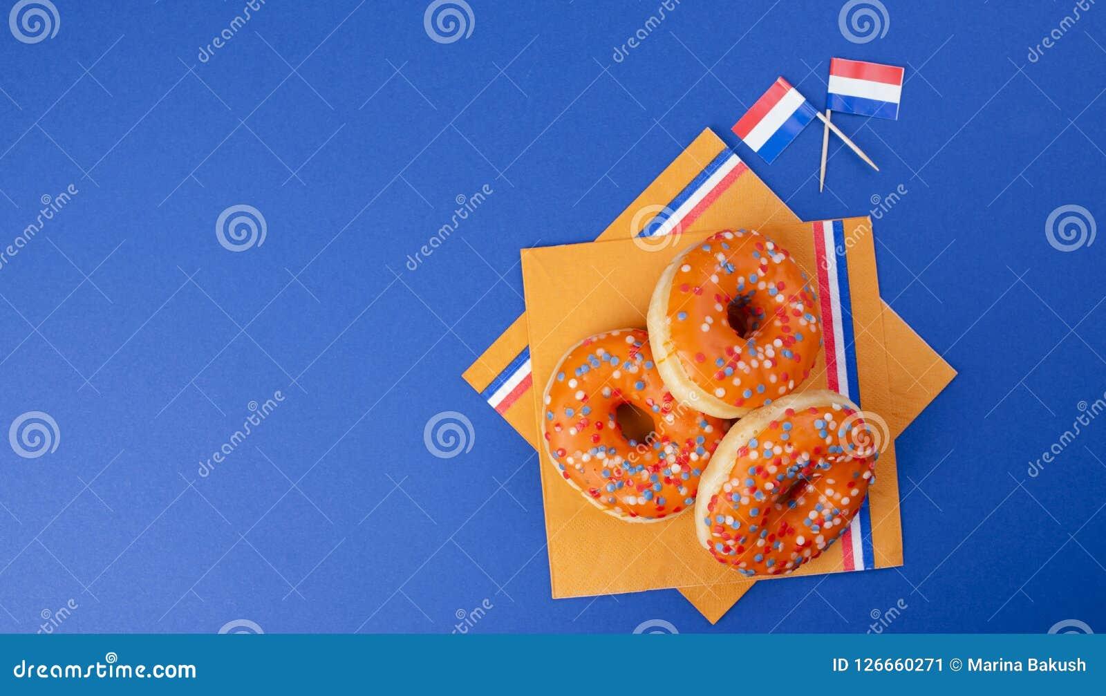 Pomarańczowi donuts dla wakacyjnego królewiątka ` s dnia, Holandia wakacje Piec na błękitnym tle Odgórny widok kosmos kopii