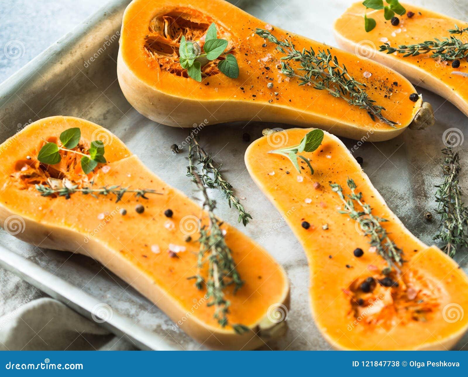 Pomarańczowy świeży dyniowy kucharstwo z pikantnością i ziele rżnięci bania plasterki na wypiekowym prześcieradle Świeża pomarańc