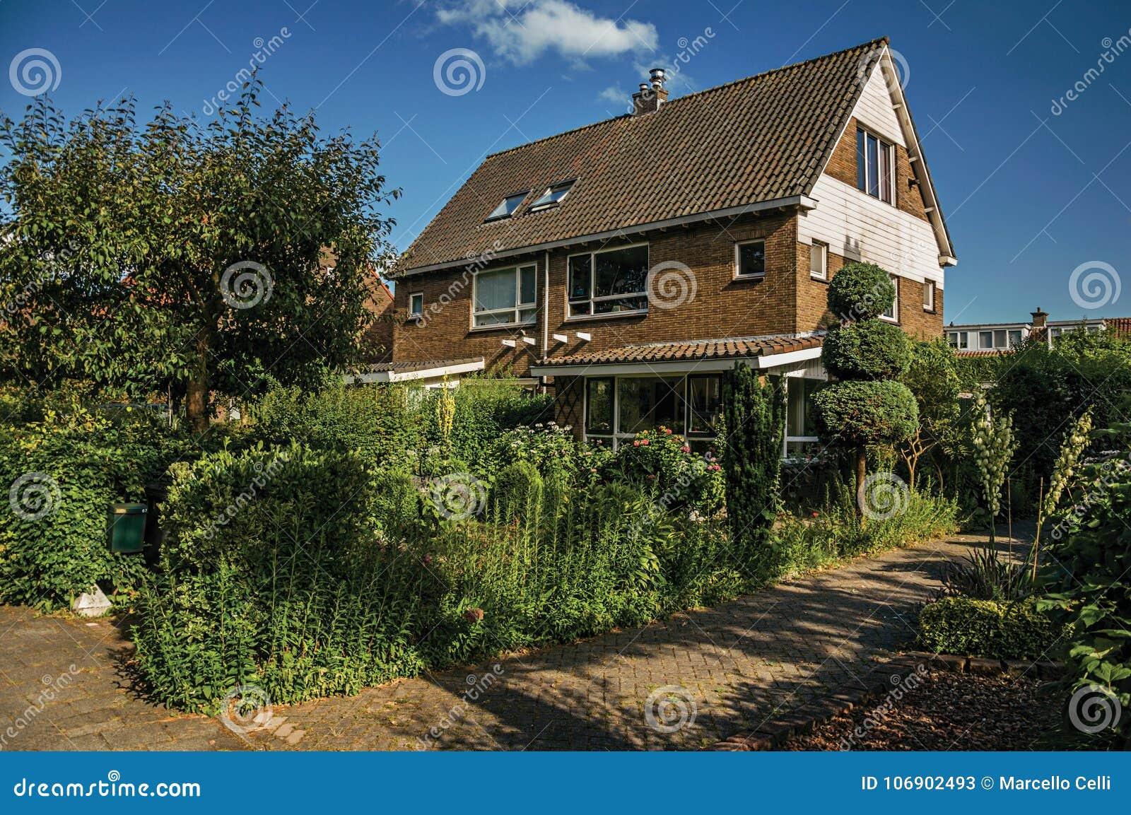 Pomarańczowy cegła dom z pięknym i zielenistym ogródem przed aleją pod niebieskim niebem przy Weesp