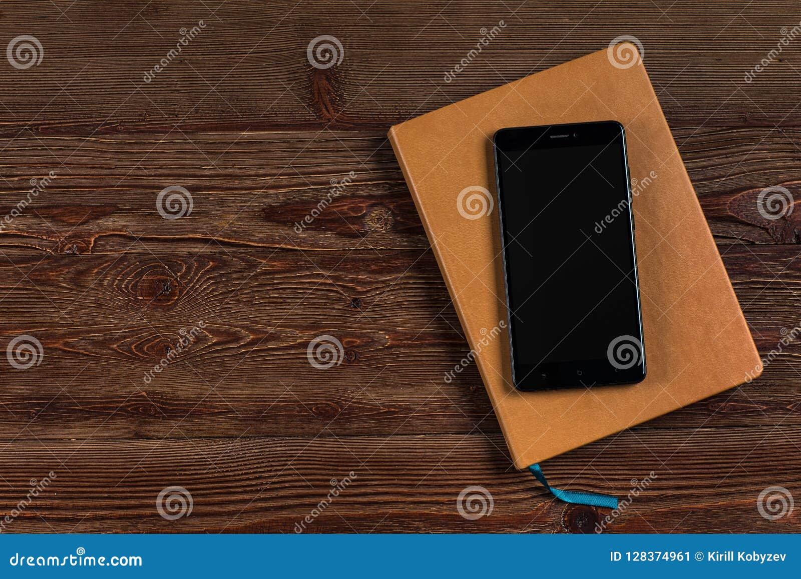 Pomarańczowy dzienniczek z czarnym telefonem