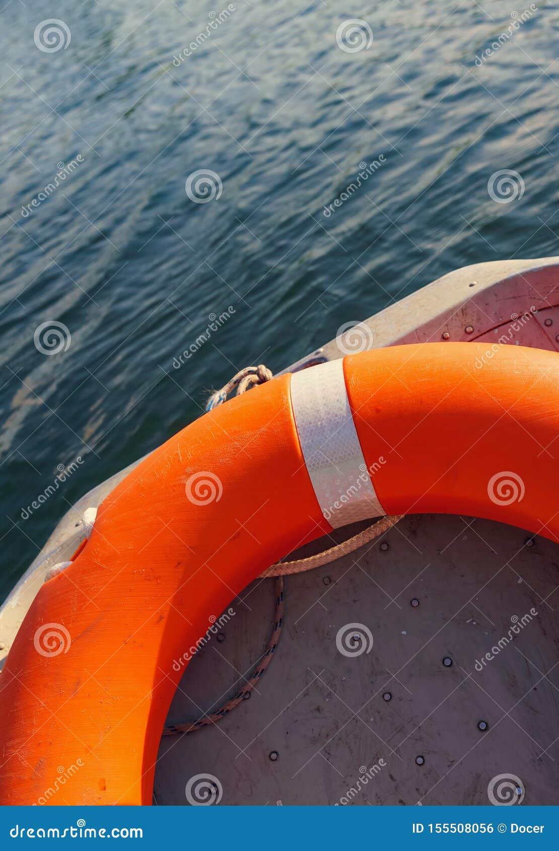 Pomarańczowy lifebelt lying on the beach w łodzi